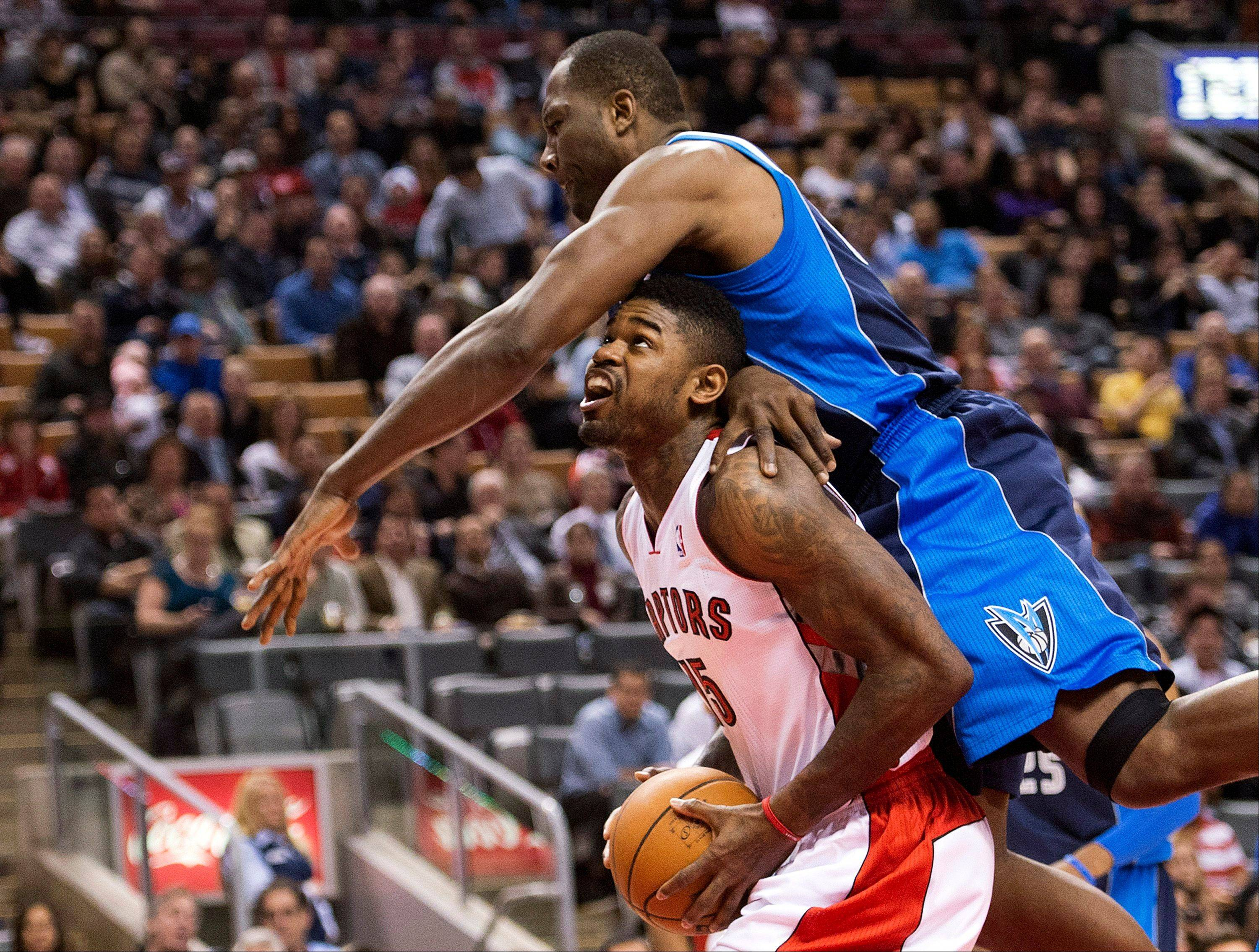 Toronto Raptors forward Amir Johnson, bottom, tries to drive to the net past Dallas Mavericks forward Elton Brand, top, Friday during first half in Toronto.