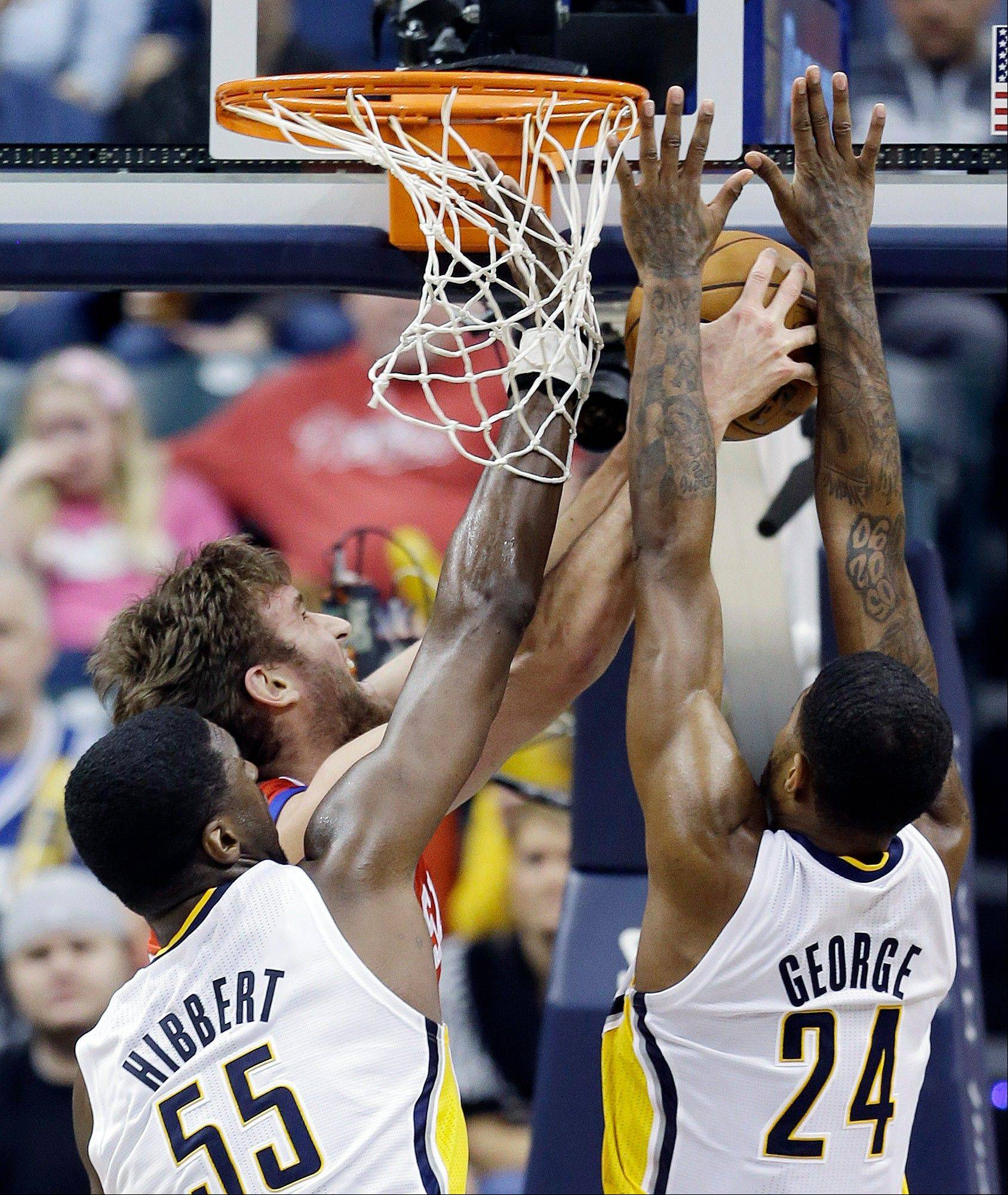 The Philadelphia 76ers� Spencer Hawes, second from left, puts up a shot against Indiana Pacers center Roy Hibbert and Paul George Friday during the second half in Indianapolis. The Pacers defeated the 76ers 95-85.