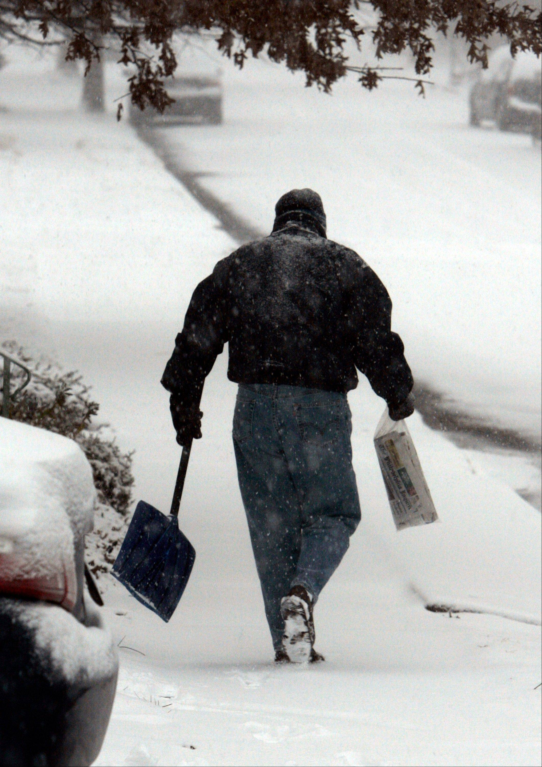 Bill Winterle carries his neighbor's newspaper to her doorstep while shoveling his driveway during a major winter storm in Havertown, Pa. Make sure packages and newspapers aren't sitting in your driveway day after day while you're away for the holidays will help deter thieves.