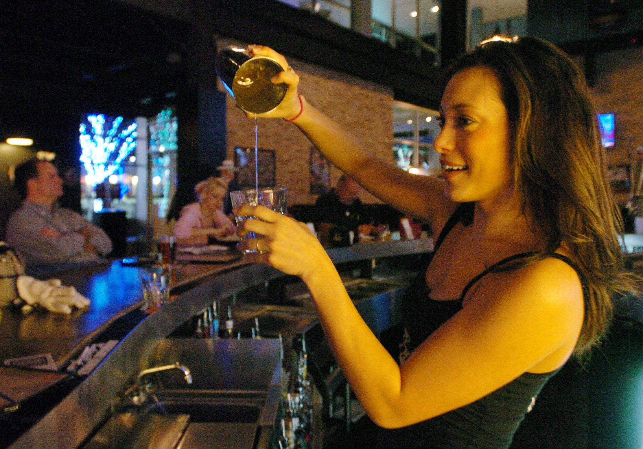 """Whiskey girl"" Brooke Miner pours a Southern Hurricane at Toby Keith's I Love This Bar & Grill in Rosemont."