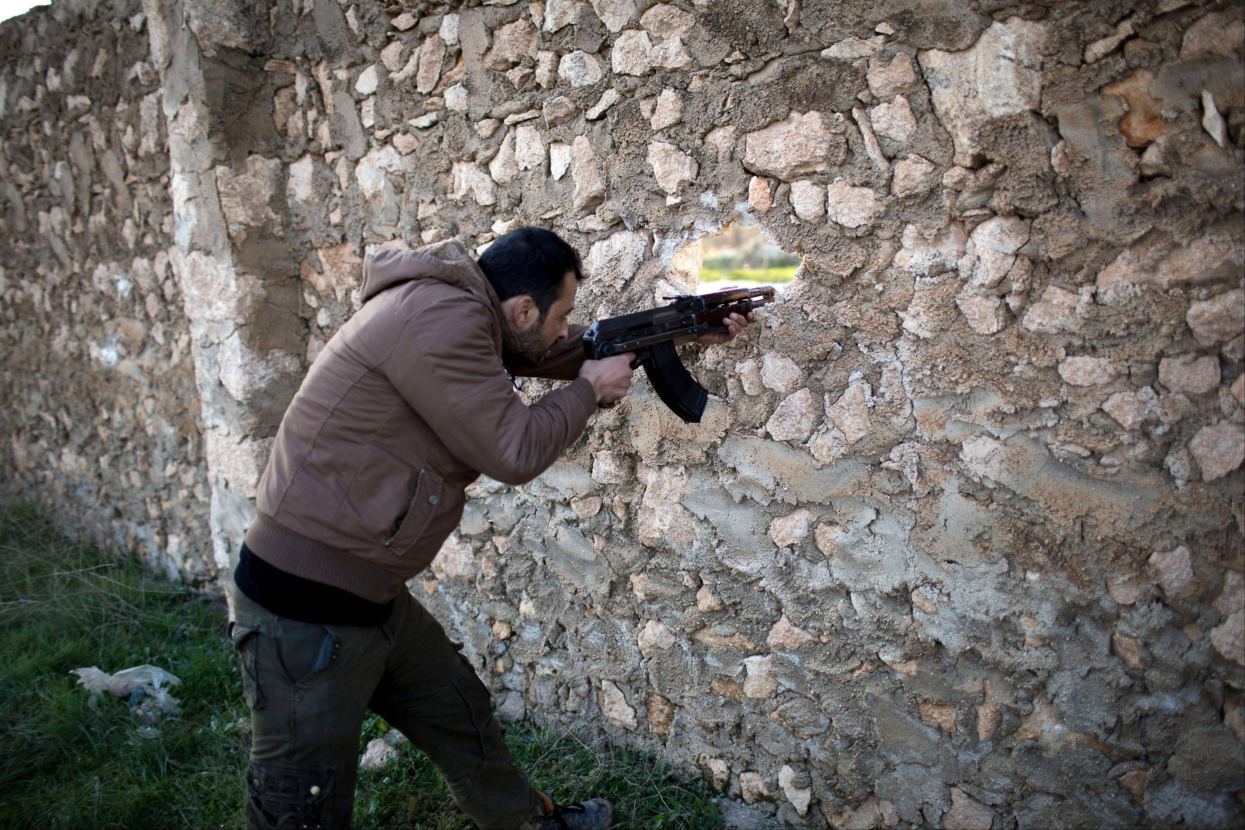 A Free Syrian Army fighter fires at Syrian Army positions Friday in Tal Sheer, Aleppo province, Syria.