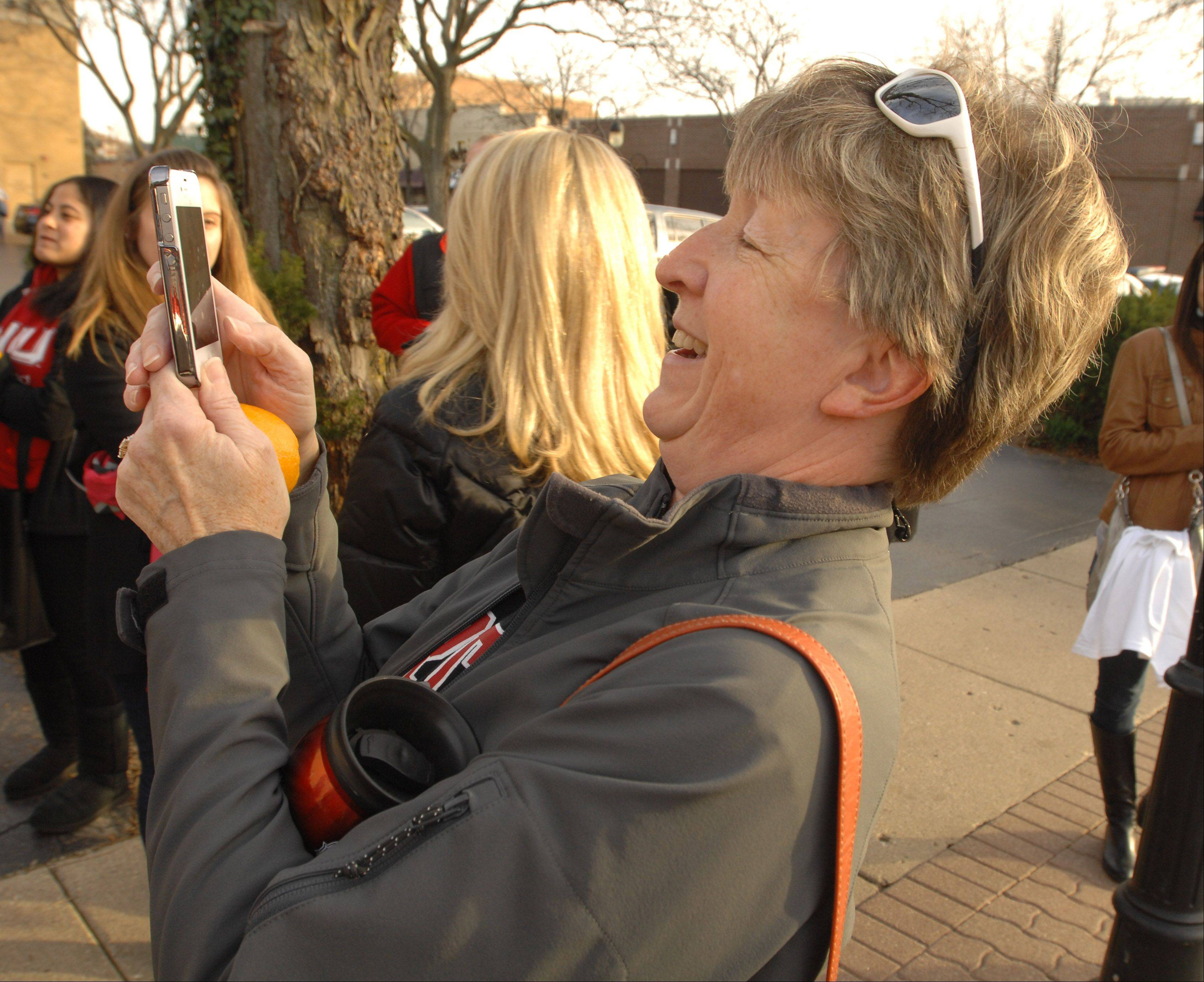 Sue Ekkebus of Naperville stops Friday to take a photo of a group of Northern Illinois University students, along with mascot Victor E. Huskie. The students were promoting the football team's Jan. 1 trip to the Orange Bowl and handing out oranges to fans.
