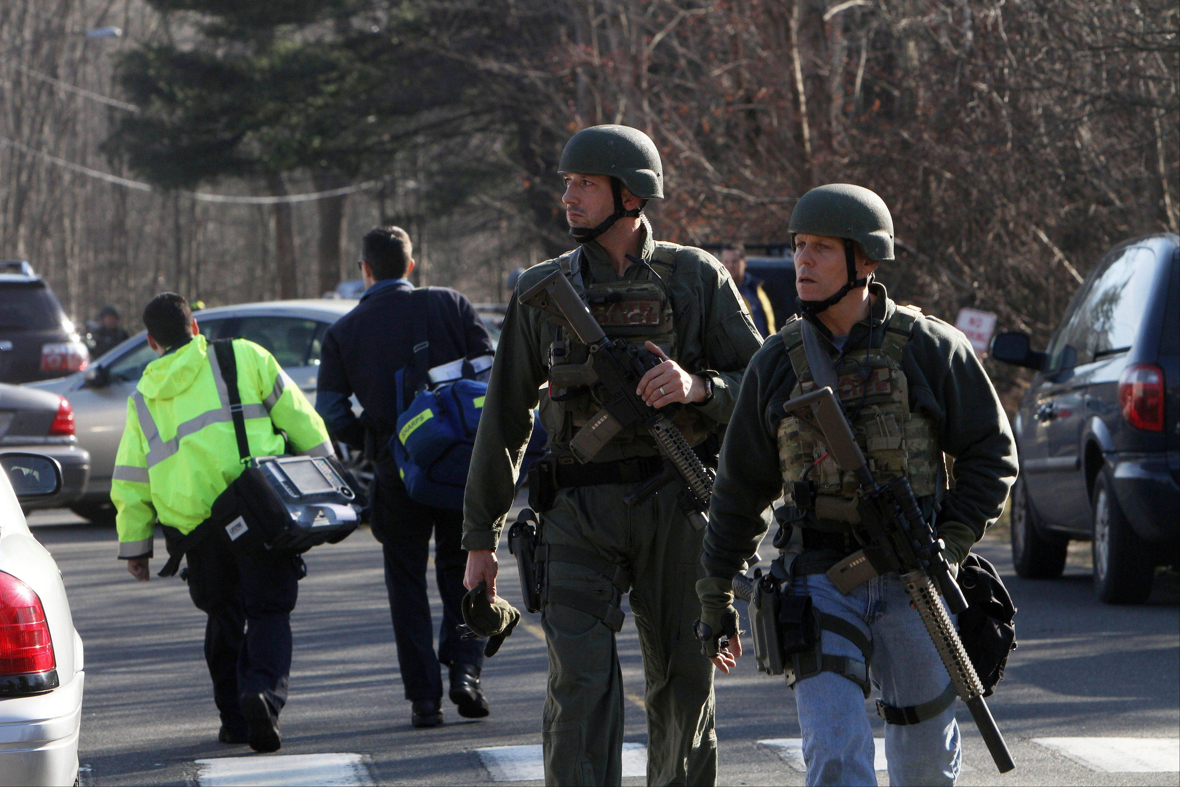 Heavily armed Connecticut State troopers are on the scene at the Sandy Hook School following a shooting at the school, Friday, Dec. 14, 2012 in Newtown, Conn.