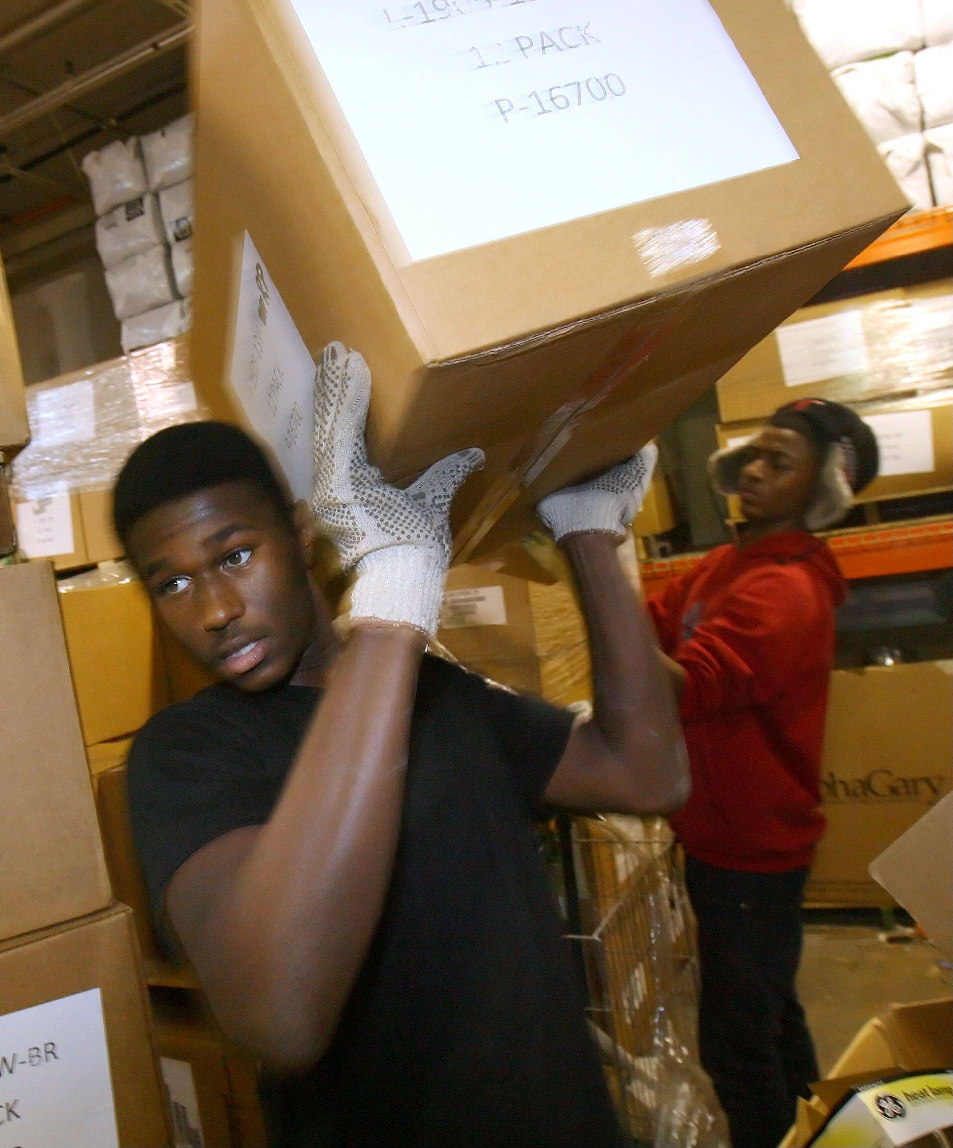 Mundelein High School sophomore Antonio Miles, left, and junior Chance Lindsey carry boxes of fluorescent light bulbs as the members of the Black Student Union volunteered their time at ReStore in Gurnee Friday.