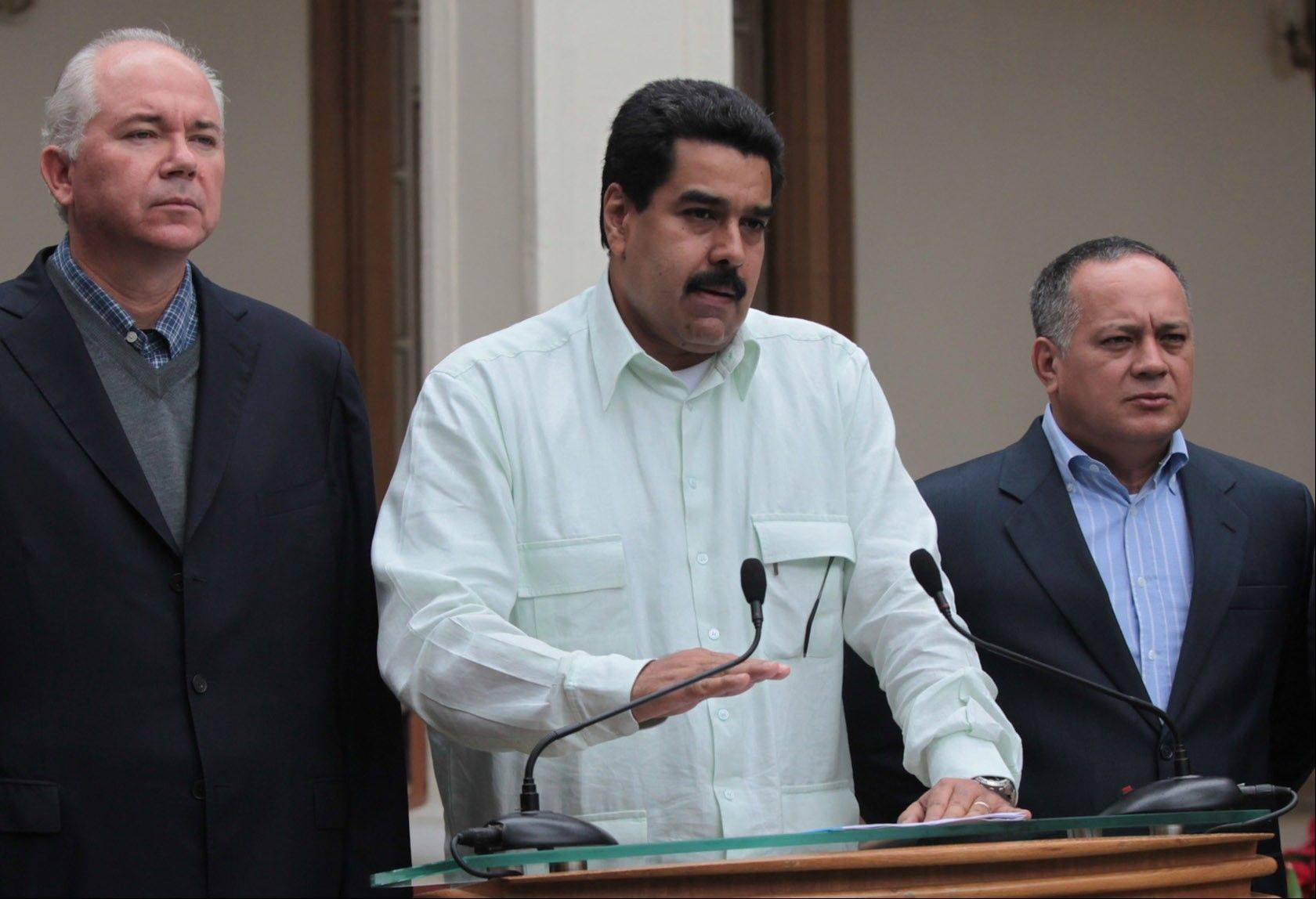 Venezuela's Vice President Nicolas Maduro, center, addresses the nation on live television flanked by Oil Minister Rafael Ramirez, left, and National Assembly President Diosdado Cabello at Miraflores presidential palace in Caracas, Venezuela, Wednesday, Dec. 12, 2012. Over the weekend, President Hugo Chavez named Maduro as his chosen political heir.
