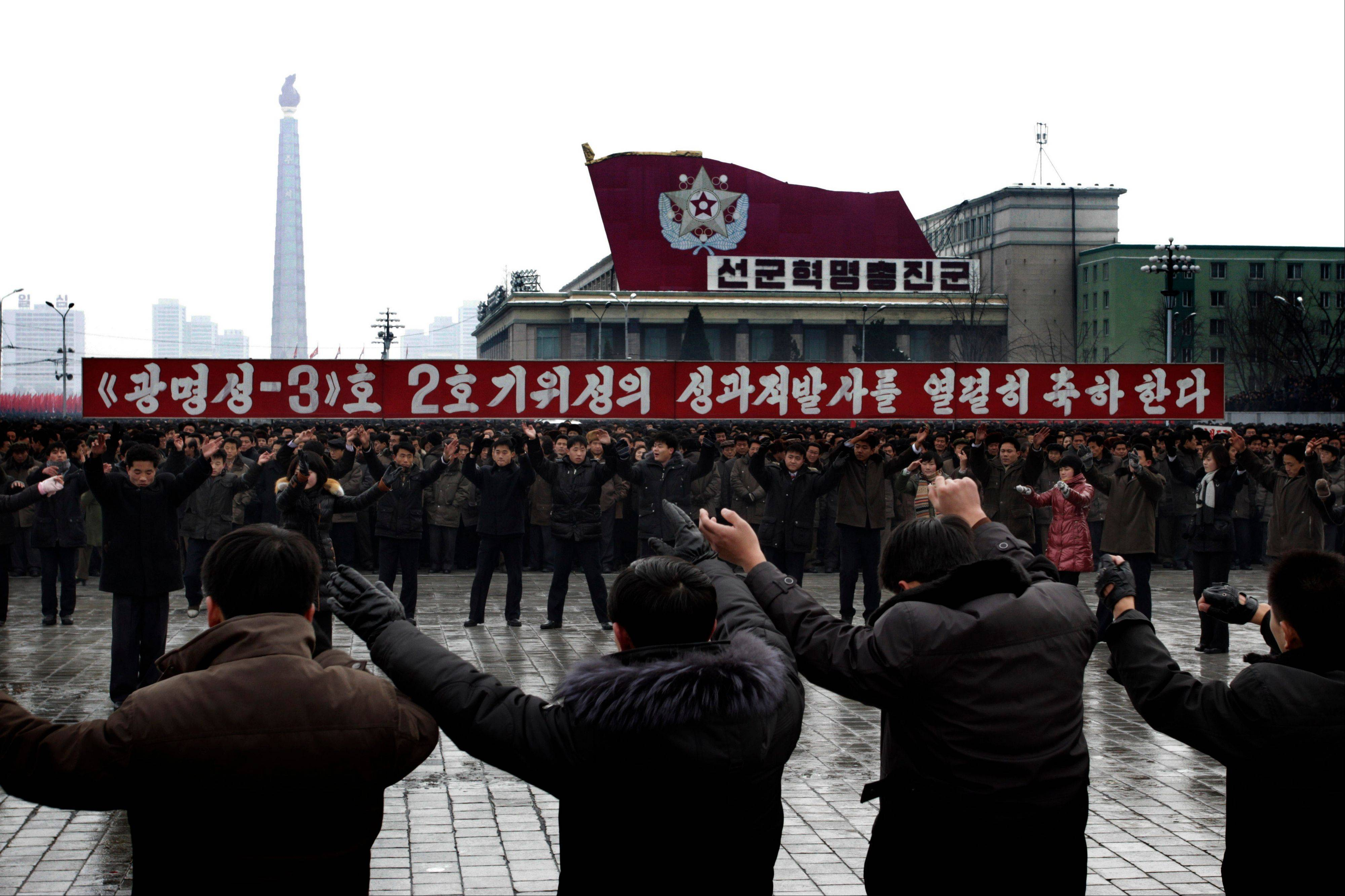 "North Koreans dance near a slogan which reads ""(we) fervently celebrate the successful launch of the second version of the Kwangmyongsong-3 satellite"" during a mass rally organized to celebrate the success of a rocket launch that sent a satellite into space, on Kim Il Sung Square in Pyongyang, North Korea, Friday, Dec. 14, 2012. As the U.S. led international condemnation of what it calls a covert test of missile technology, top North Korean officials denied the allegations and maintained the country's right to develop its space program."