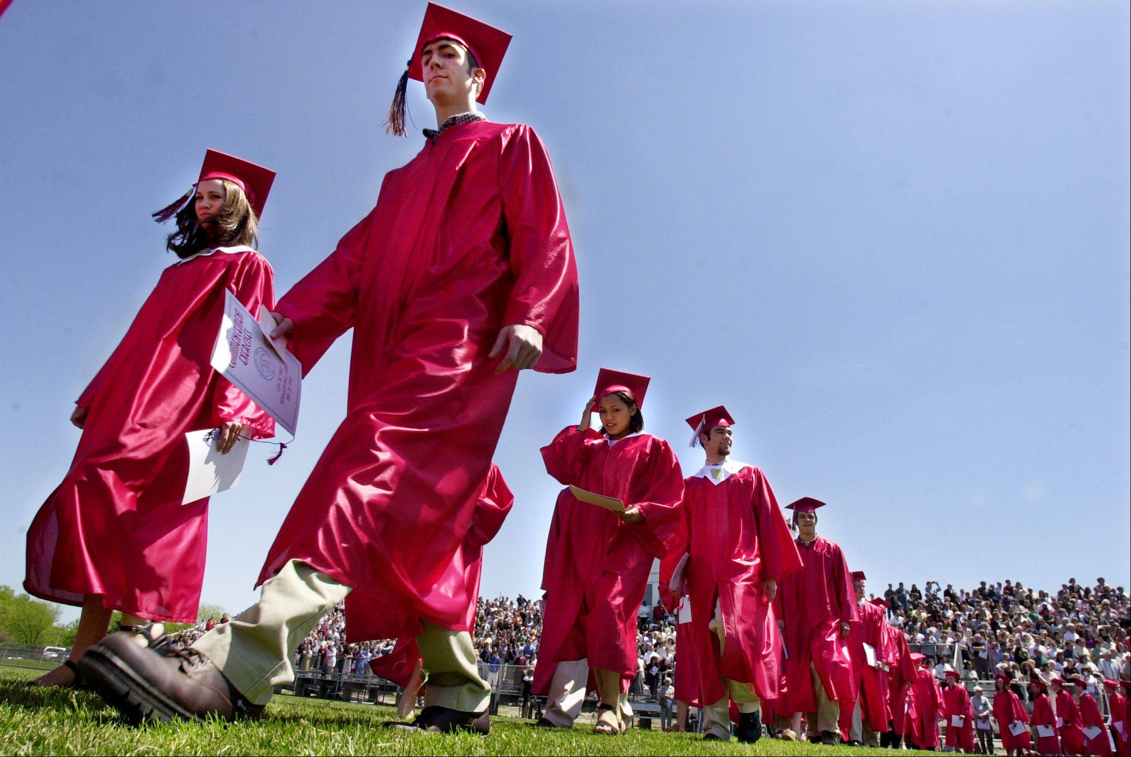 Graduates at Mundelein high stream onto the football field under perfect weather conditions Sunday.
