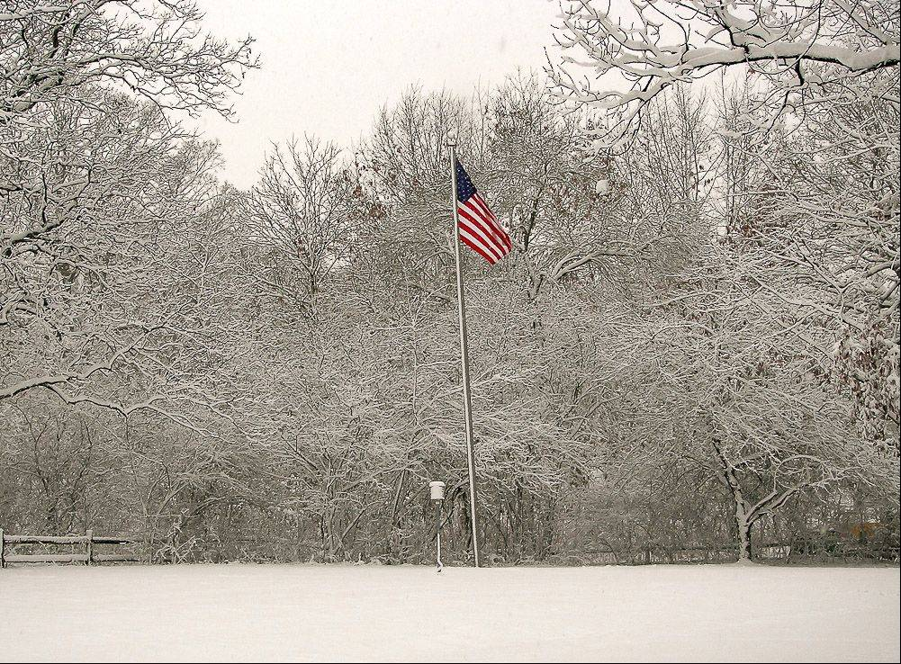 A colorful American flag waves in a snowy, white landscape.