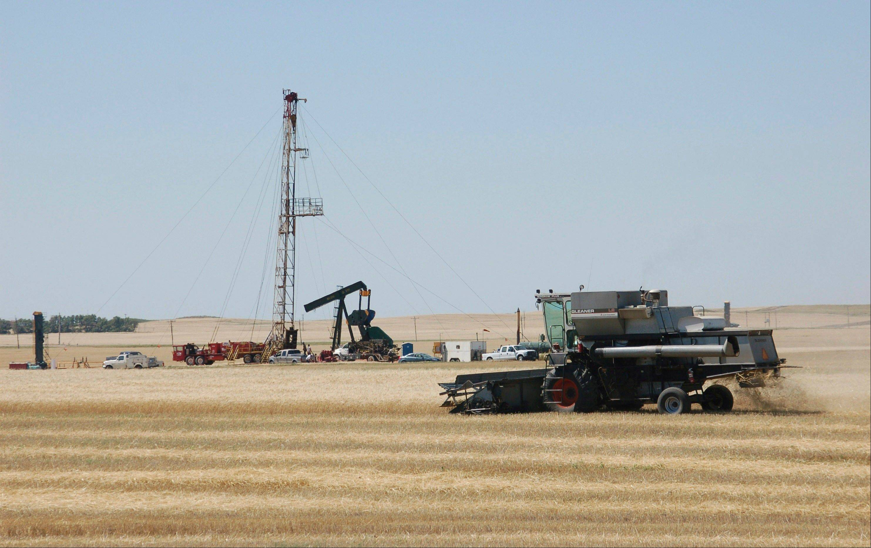 A combine cuts durum near an oil well in Tioga, N.D. The worries about what drilling does to the air are both global and local, with scientists concerned about the effects on climate change as well as the possible health consequences from breathing smog, soot and other pollutants.