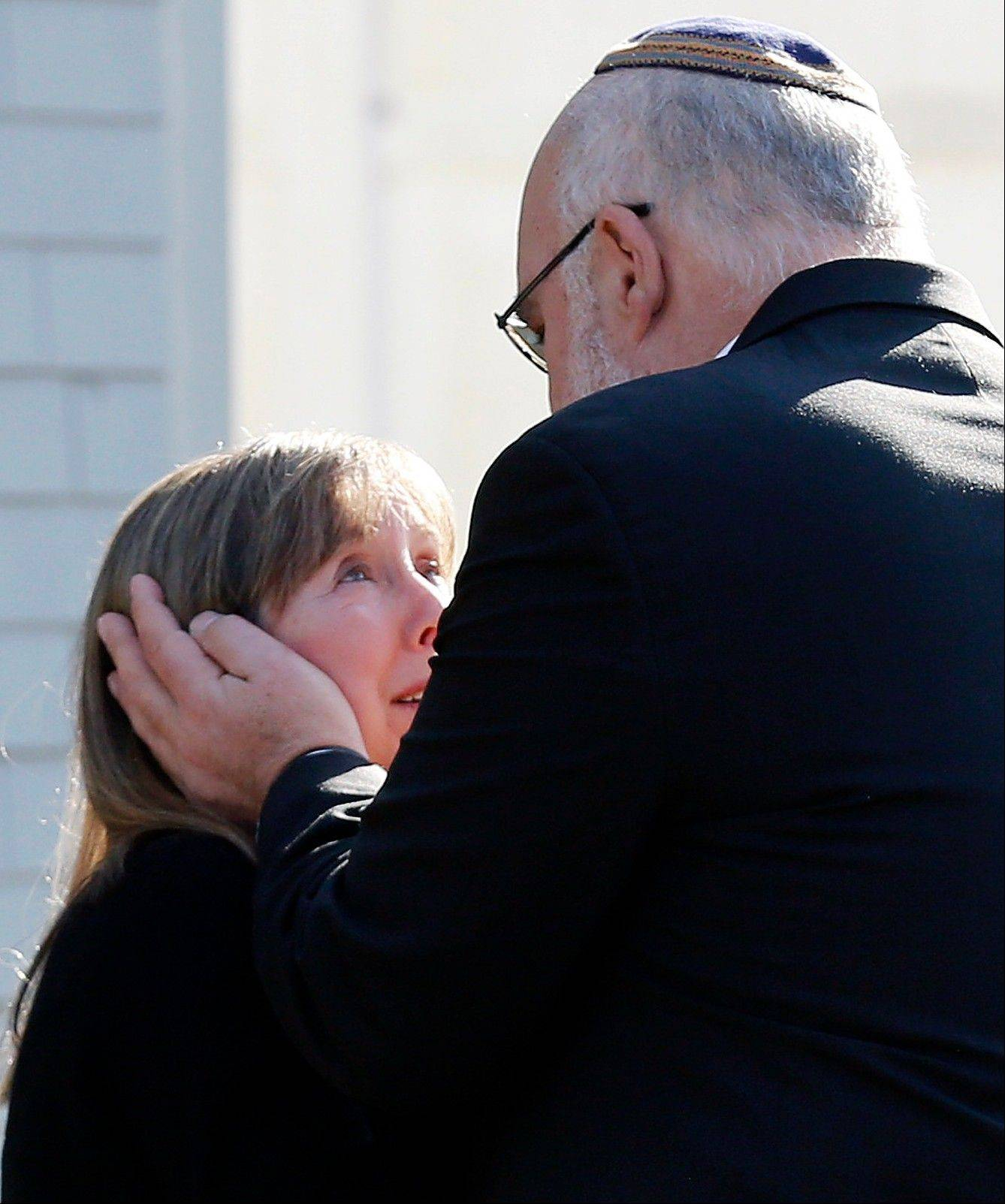 Two people embrace following a service at the Congregation Adath Israel in Newtown, Conn., Saturday. Rabbi Shaul Praver said a six-year-old boy from the congregation was a school shooting victim and that he would be buried on Sunday.