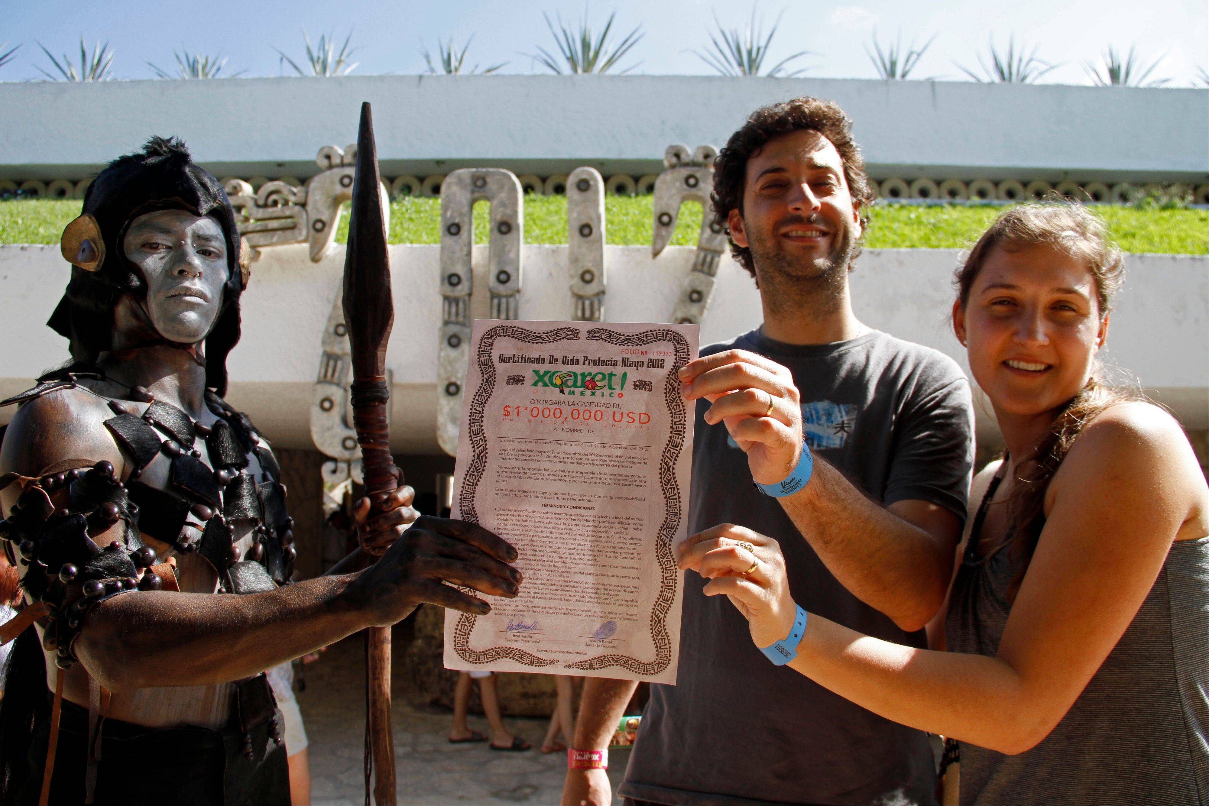A man dressed as a Mayan warrior delivers a life certificate for one million dollars, to be paid in case the world comes to an end to an unidentified couple, as they pose for a photo at the Xcaret theme park Saturday in Playa del Carmen, Mexico.