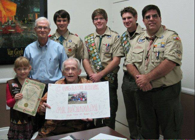 Robert Buchanan, seated, displays a card from Boy Scout Troop 43 of Batavia where he received his Eagle Scout rank. Clare Buchanan holds the 1933 Batavia Troop 3 charter, which has her grandfather�s name on it. Standing, from left, are Buchanan�s brother Willard Buchanan; Drew Cunningham, Life Scout and senior patrol leader of Troop 33, Redlands, Calif.; Eagle Scouts Nathan Price and Conor Frasher; and Shawn Price, Eagle Scout and Troop 33 scoutmaster.