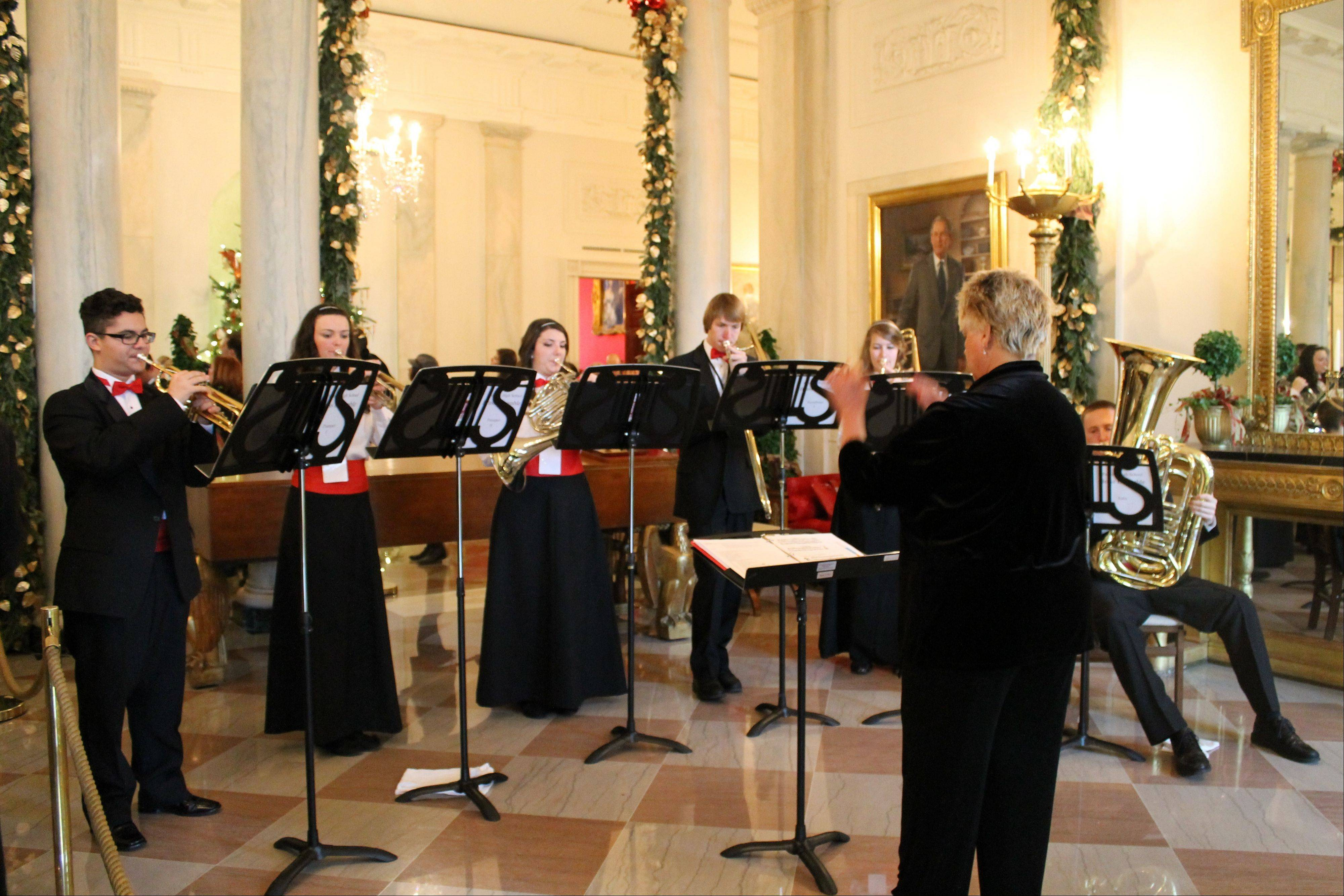 Trumpet players Jonathon Szabo and Natalie Stevens, French horn player Jenna Campbell, trombone players Joe VanBladel and Kirsten Eissman, and tuba player Ken Cervenka of the Palatine High School Brass Ensemble perform Saturday at the White House under the direction of conductor Raeleen Horn.