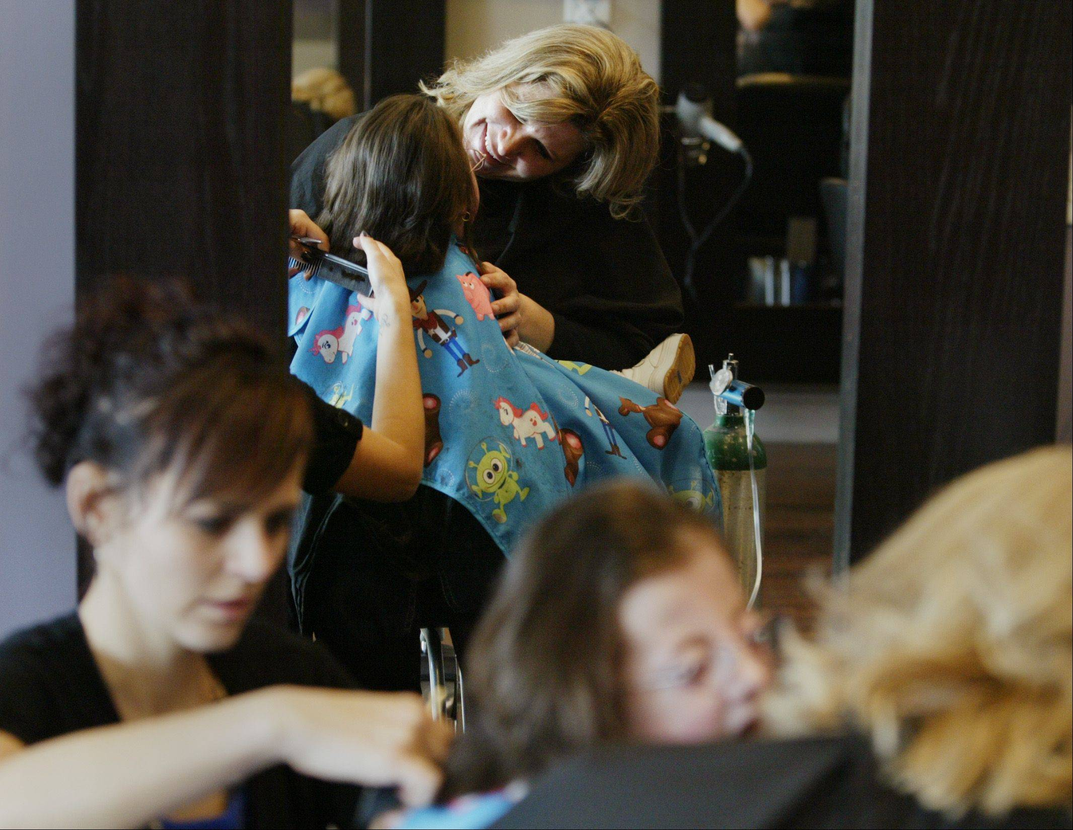 Kelly Whistler grins as she watches daughter Kayli get her hair cut by stylist Gina Coleman Friday at Blush Salon in Crystal Lake. Kayli, who has Trisomy 18, is donating her hair to Wigs for Kids.