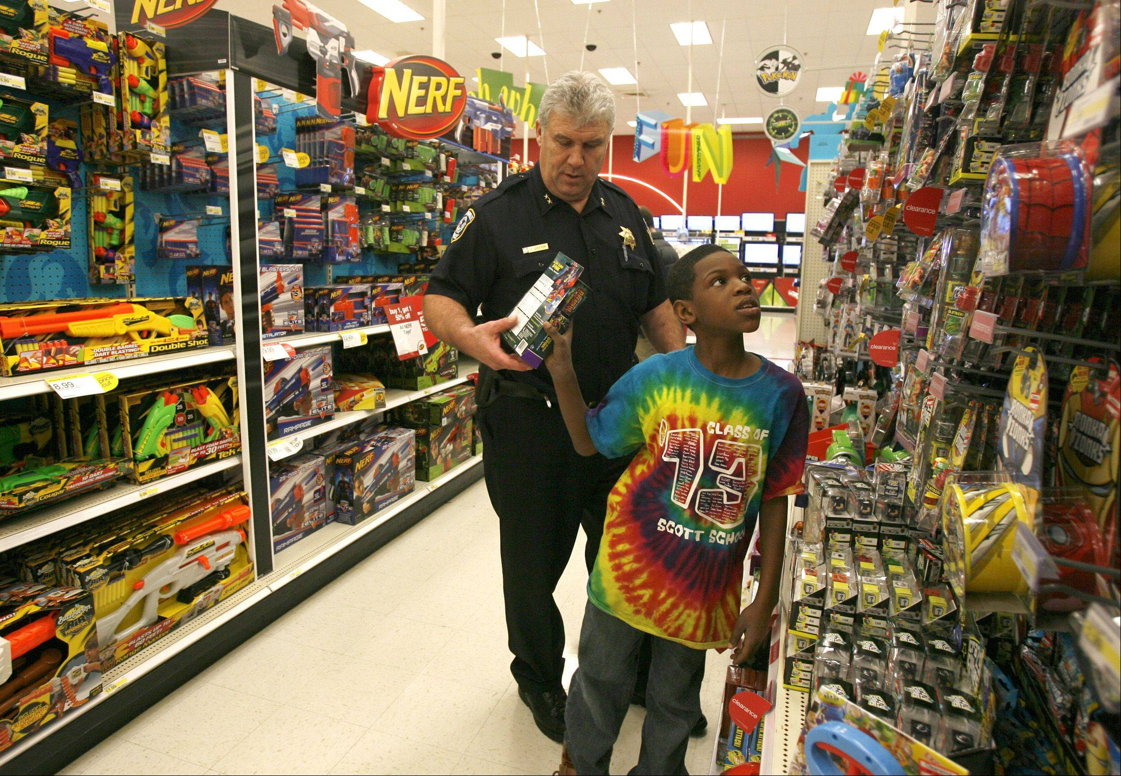 Darrell Ware, 10, of Naperville is teams up with Naperville Deputy Chief John Gustin, who guides a shopping spree at a Naperville Target Store. The NFOP in conjunction with the City of Naperville�s youth services unit, selected several children to participate in a $150.00 shopping spree.