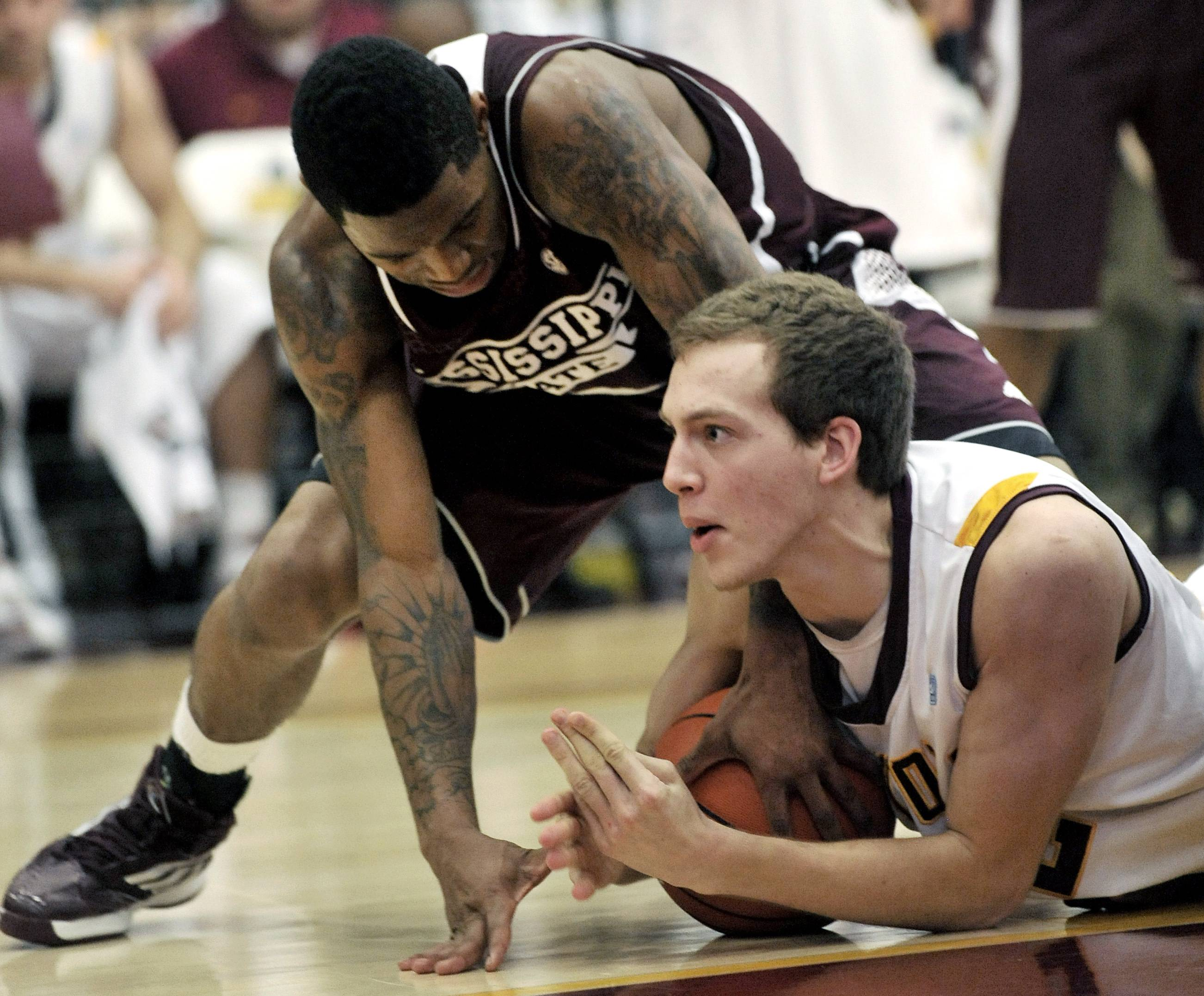 Loyola's Matt O'Leary, right, battles Mississippi State's Trivante Bloodman, left, for a loose ball Saturday during the first half in Chicago. Loyola won 59-51.