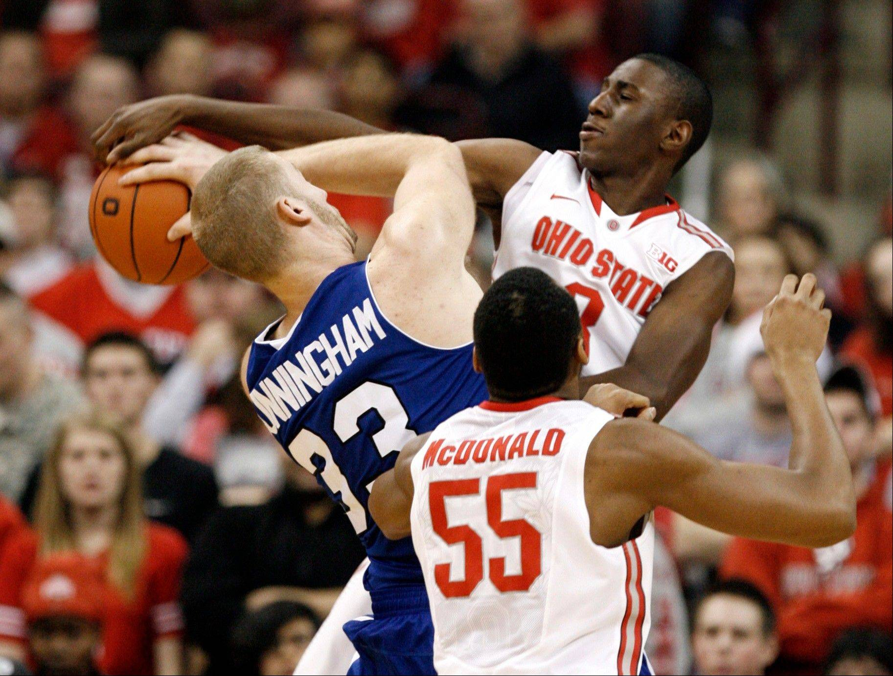 Ohio State�s Shannon Scott, right, fouls UNC-Asheville�s D.J. Cunningham, left, as Ohio State�s Trey McDonald looks on Saturday during the second half in Columbus, Ohio. Ohio State won 90-72.