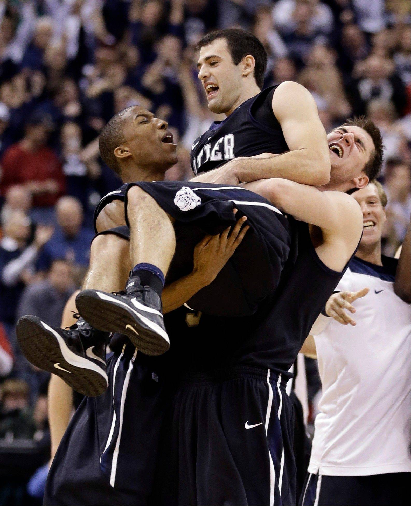 Butler guard Alex Barlow, center, is carried by forward Kameron Woods, left, and center Andrew Smith Saturday after Butler defeated No. 1 Indiana 88-86 in overtime in Indianapolis.