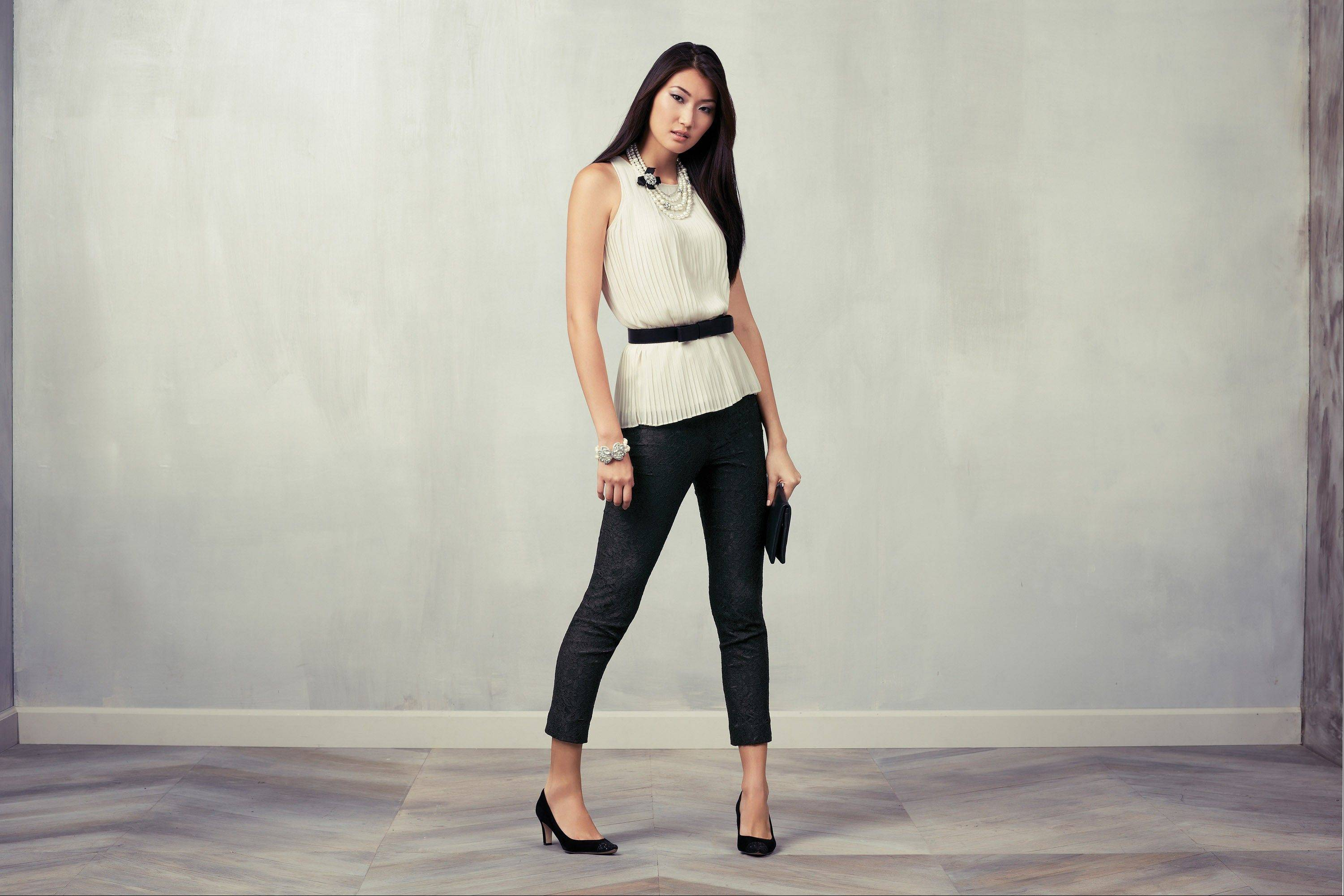 A model wears a white sleeveless blouse and black cigarette pants.
