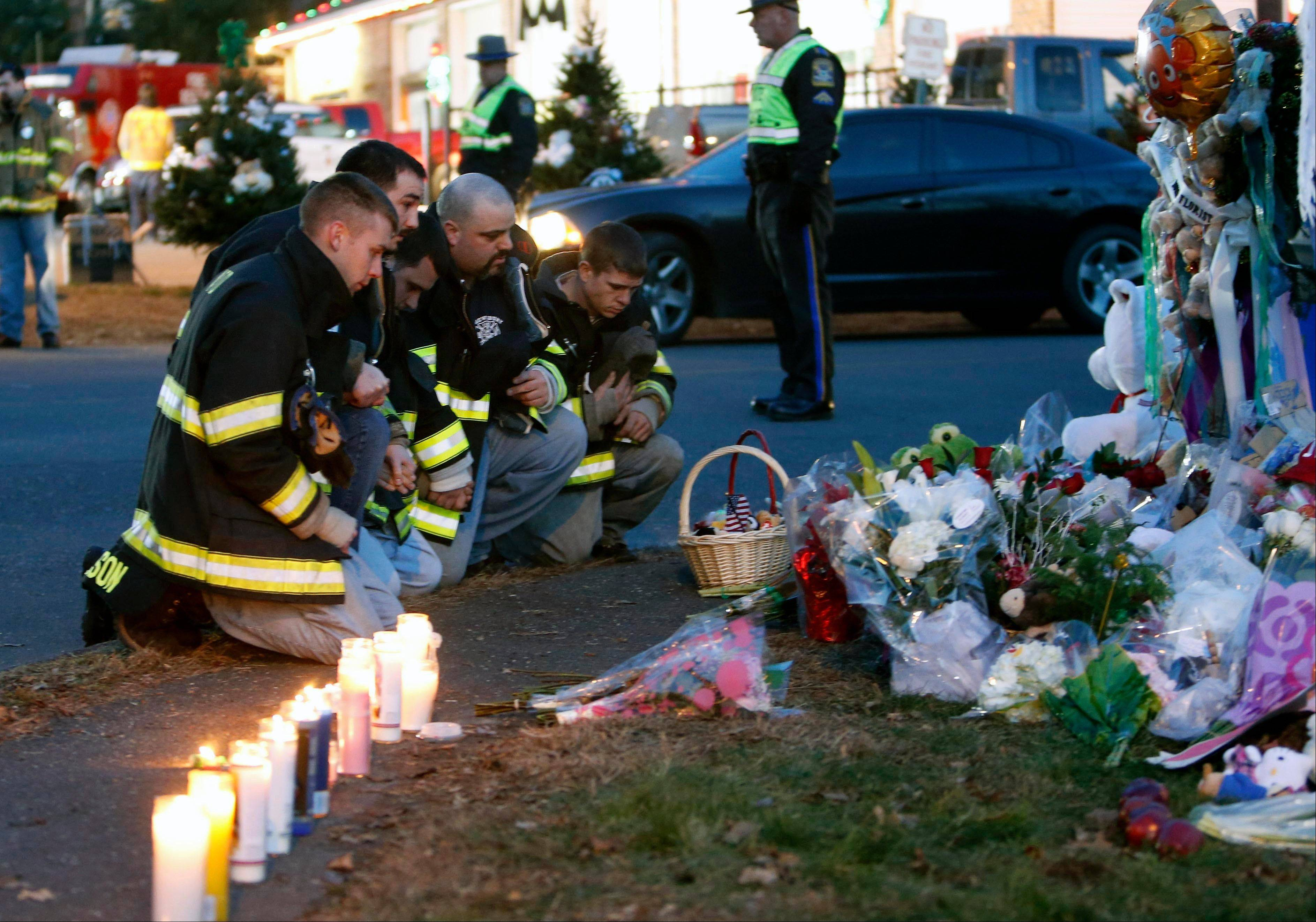 Firefighters pay their respects at a memorial for shooting victims near Sandy Hook Elementary School, Saturday.