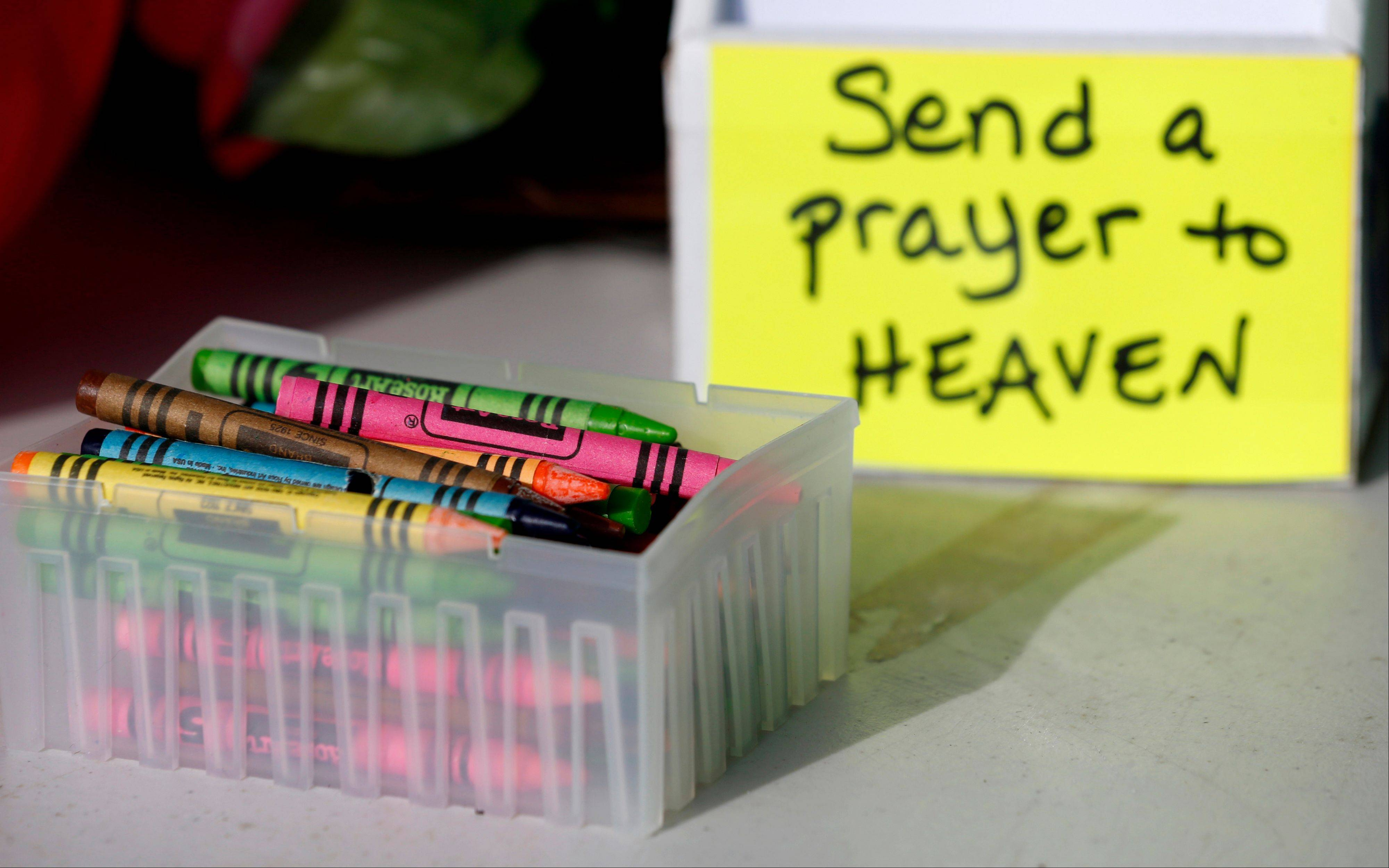Crayons sit on a table outside of a barbershop a day after a gunman opened fire at Sandy Hook Elementary School, Saturday.