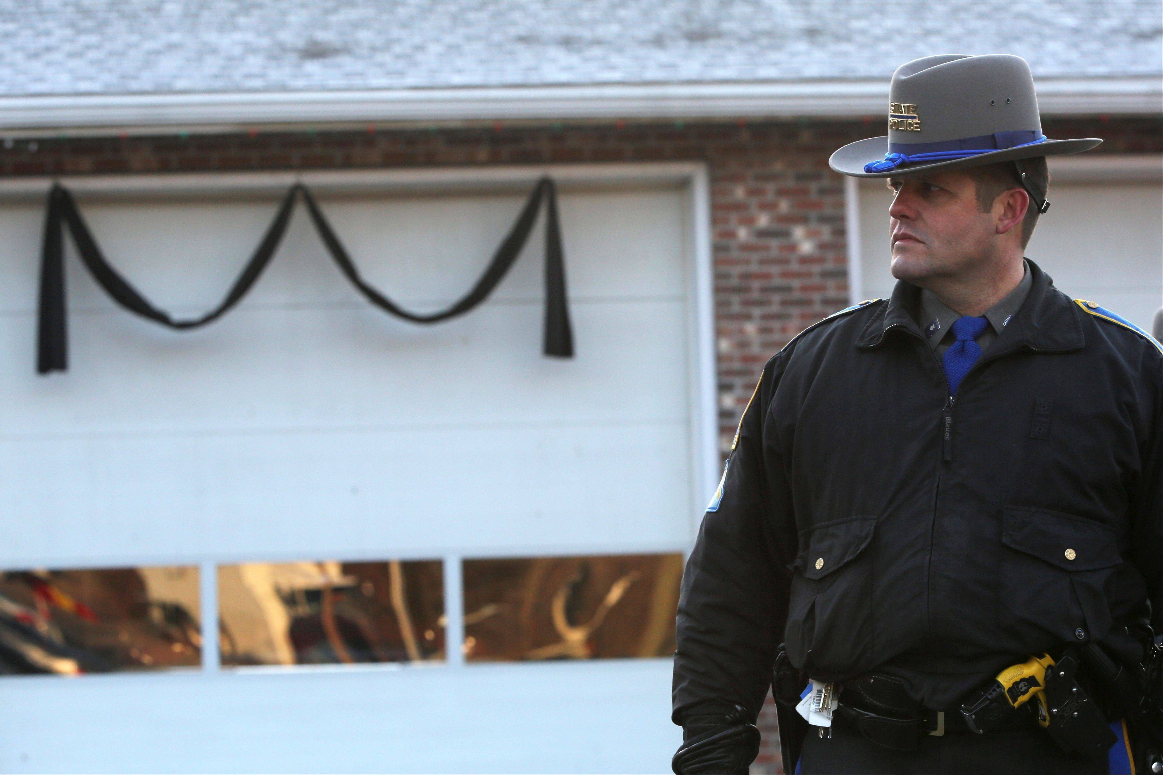 Bunting hangs on the Sandy Hook fire house as a Connecticut State Trooper stands guard outside, Saturday, Dec. 15.
