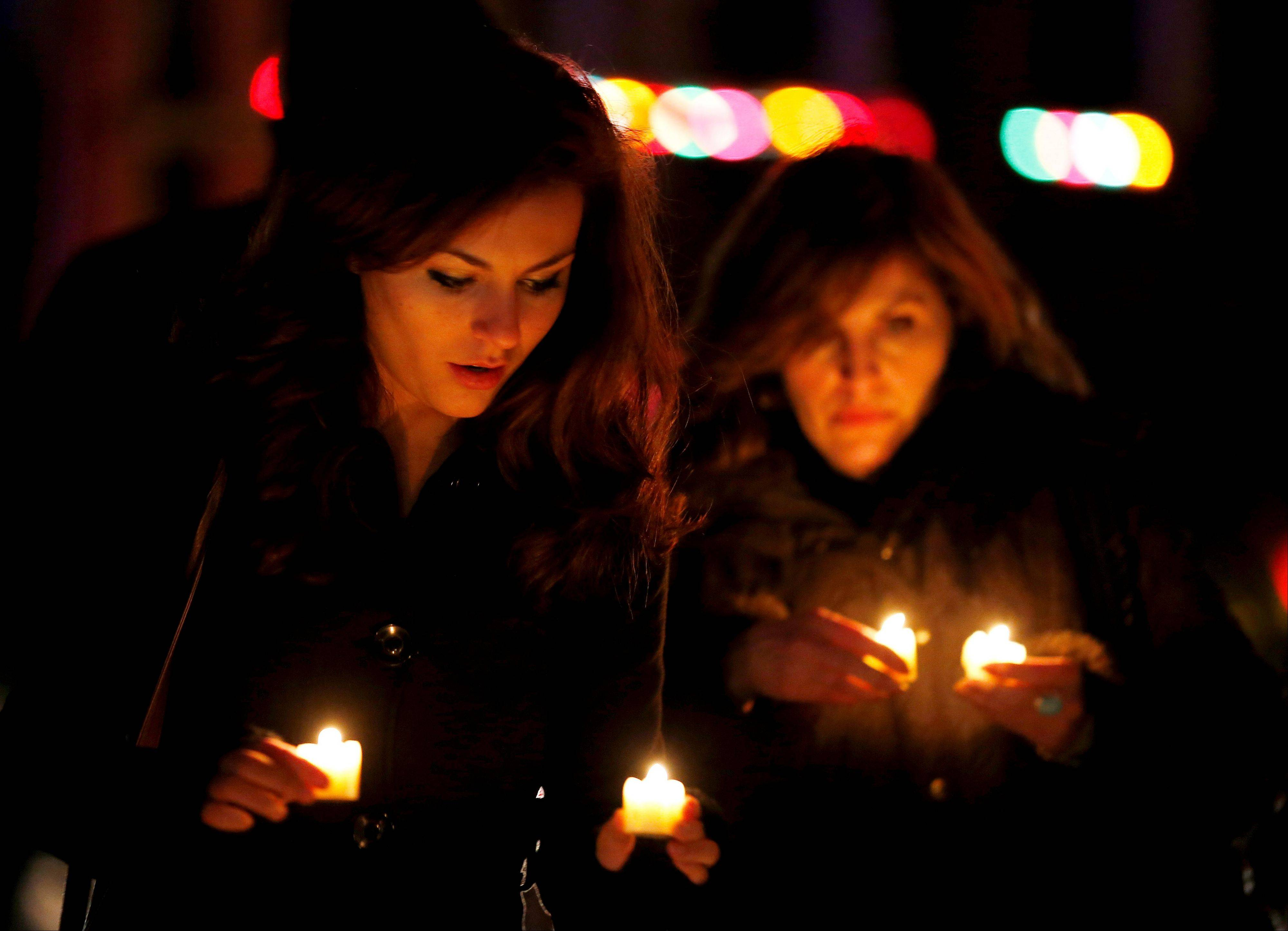Katy Caulfield, left, and her mother, Irene Caufield, hold candles to place at a makeshift memorial near the elementary school where a day earlier a gunman opened fire, Saturday.