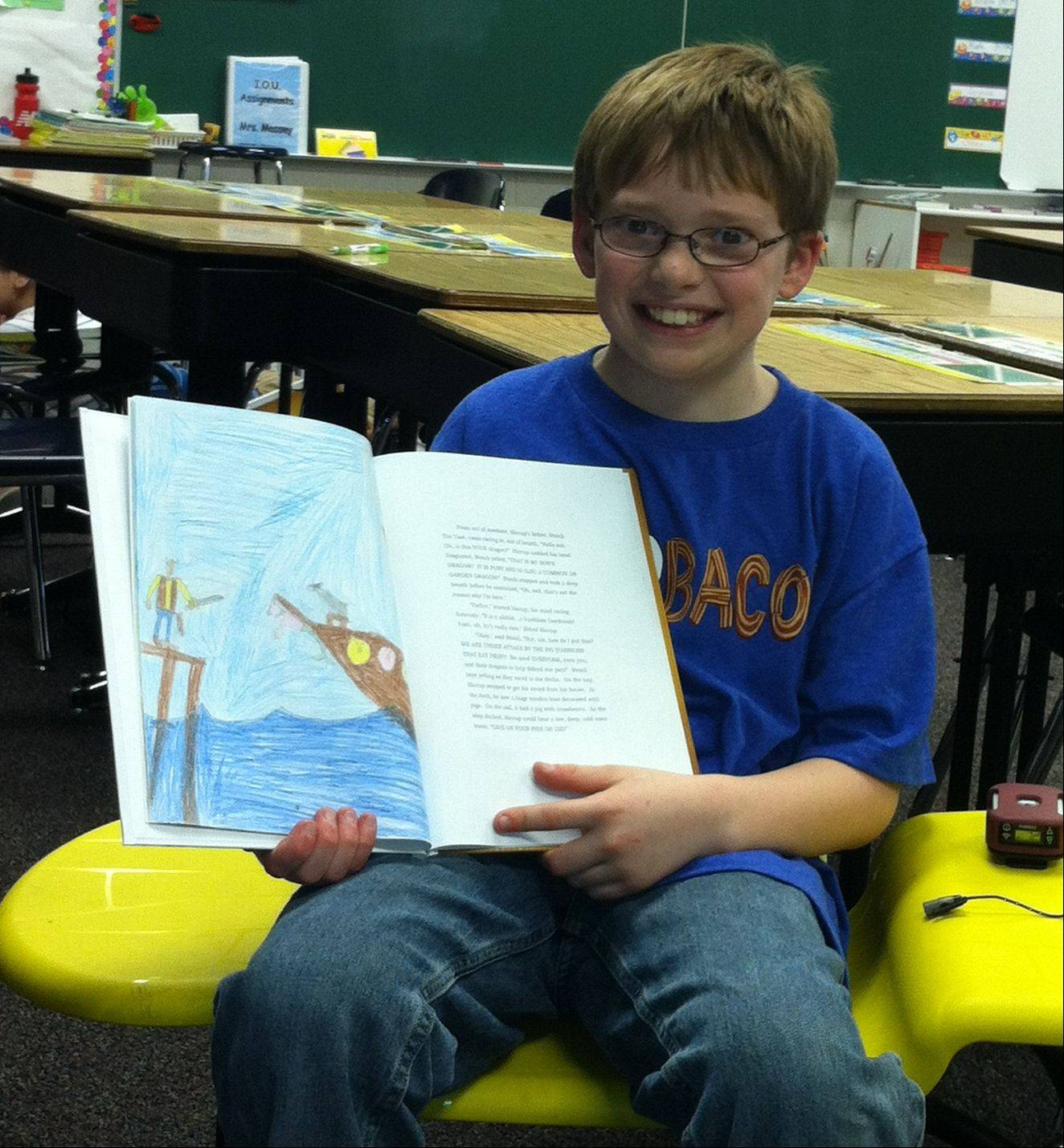 "Alex Lancaster, 12, is pictured with a book he published titled ""How to Train Your Dragon: Pies Versus Pigs."""