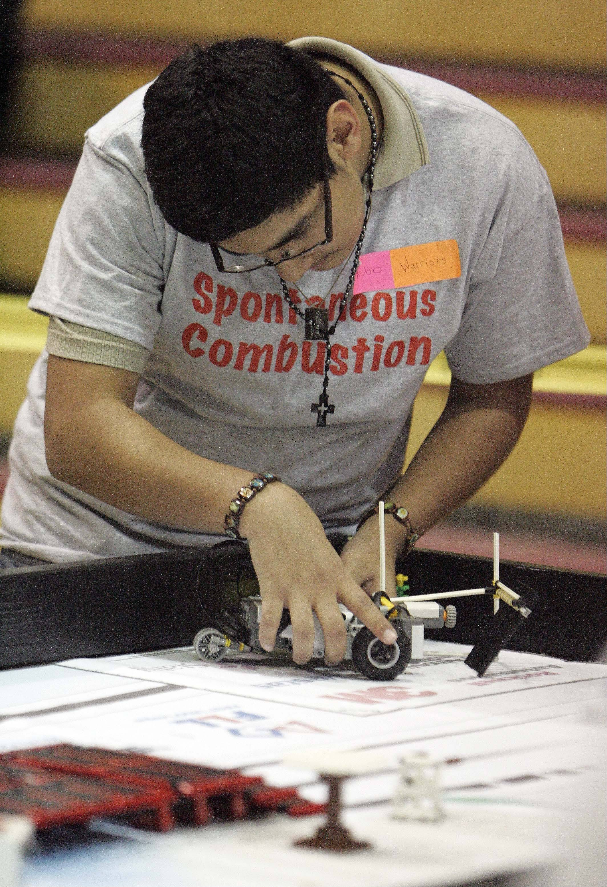 "Brian Espinosa of Abbott Middle School in Elgin prepares his team's Lego creation during the FIRST Lego League 2012 ""Super Seniors"" event at Rotolo Middle School in Batavia Saturday."