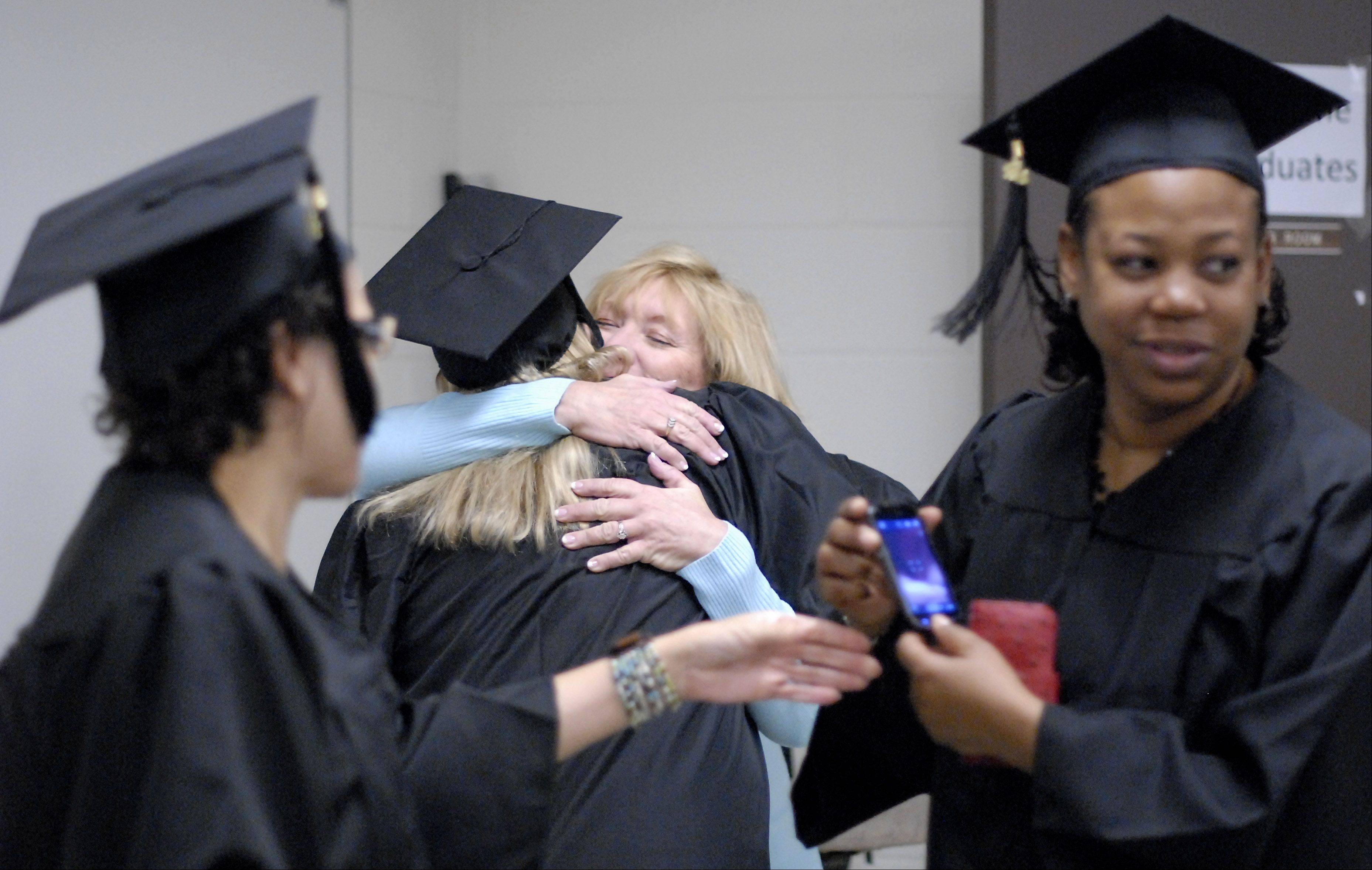 Laura Stoecker/lstoecker@dailyherald.comAs Colleen Williamson of Hanover Park passes her phone to Bridgette Sowers of Elgin for photos, Michelle Lawler of Gilberts gets a hug from her stepmother, Suzy Macino of Geneva, before the morning commencement ceremony at the Judson University chapel in Elgin on Saturday, December 15. The three graduates earned a Bachelor of Arts in Human Resource Management.