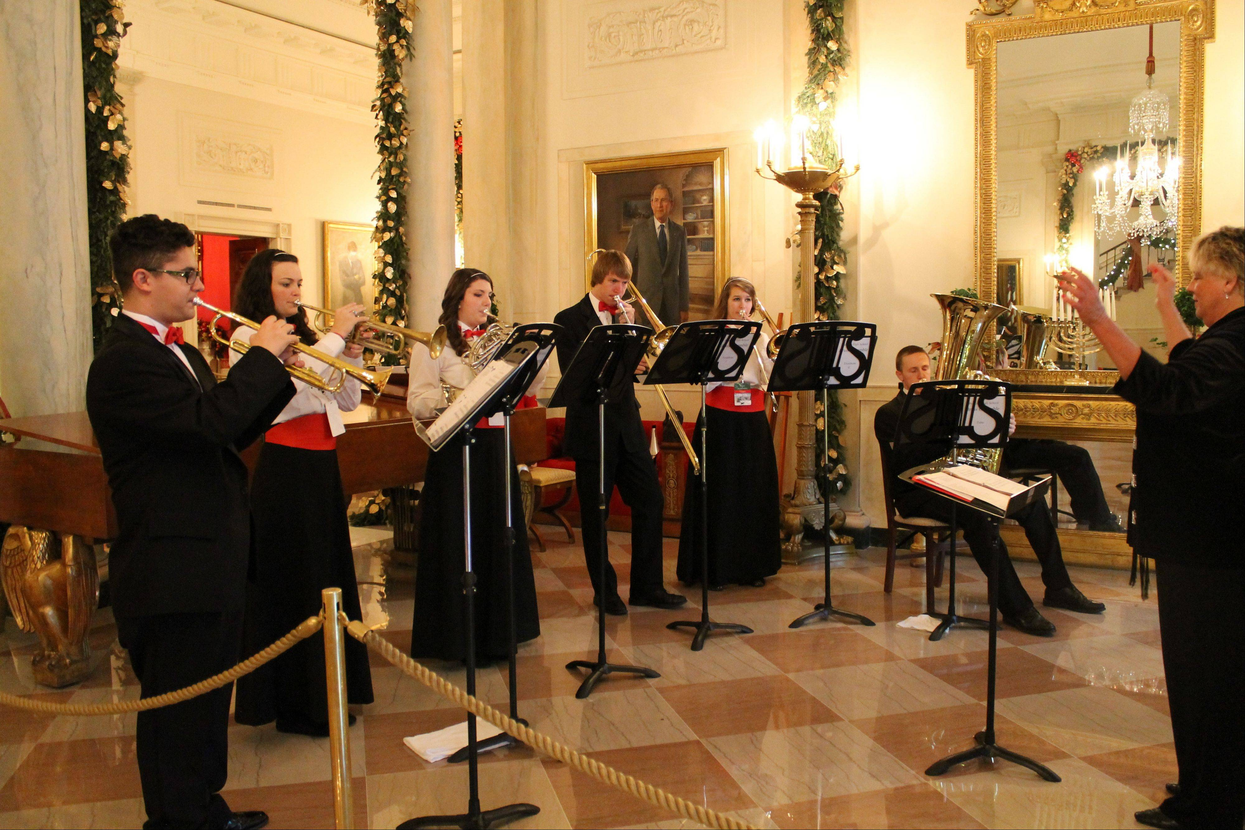 The Palatine High School Brass Ensemble performs Saturday morning in the White House grand foyer during a holiday open house. Performers Jonathan Szabo, Natalie Stevens, Jenna Campbell, Joe VanBladel, Kirsten Eissman and Ken Cervenka are under the direction of conductor Raeleen Horn.