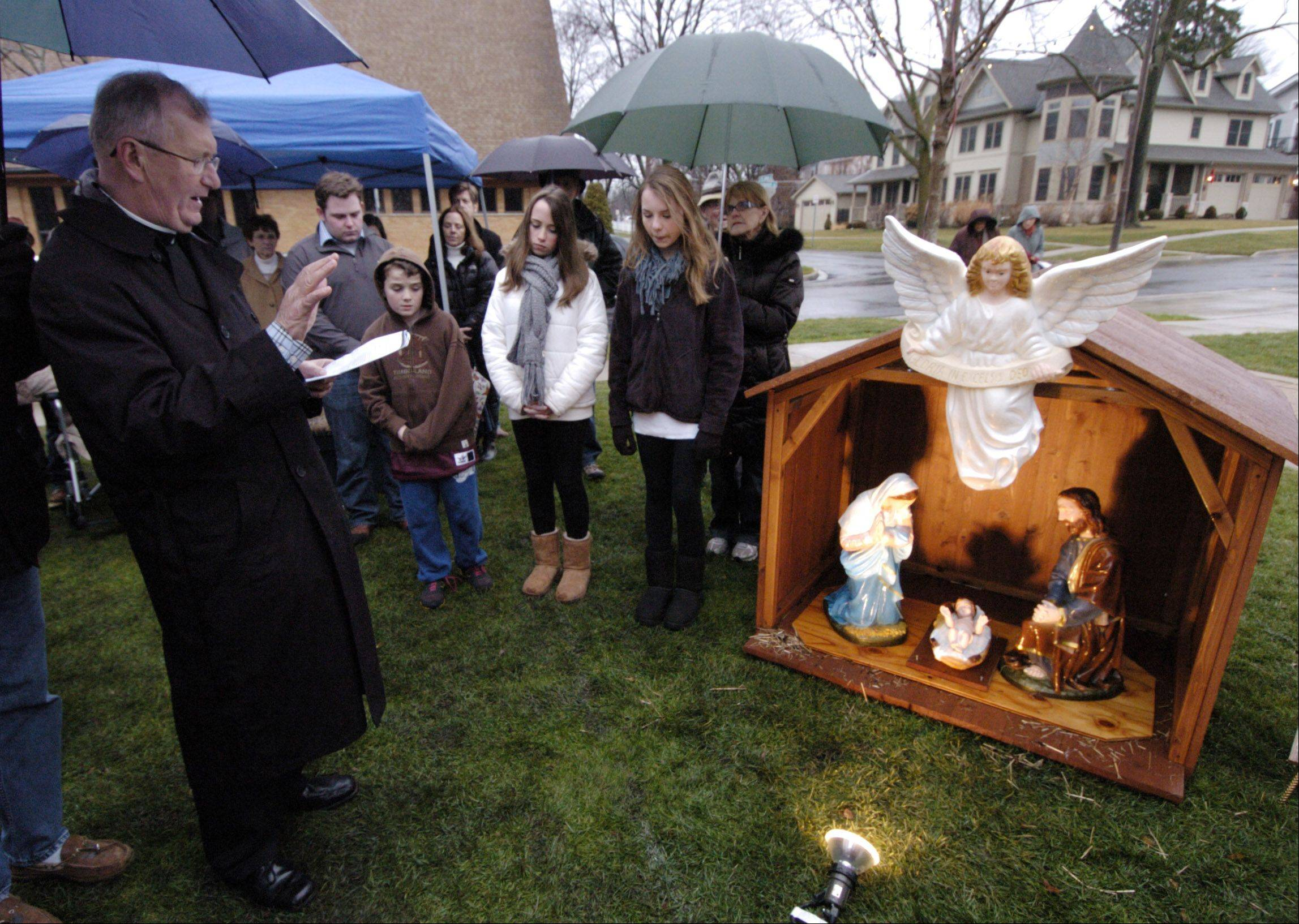 Rev. Bill Zavaski, pastor of Saint James Catholic Church in Arlington Heights, blesses the newly added Nativity scene Saturday at North School Park in Arlington Heights. The Illinois Nativity Scene Committee hosted a ceremony after receiving a permit to display the Nativity until Jan. 6.