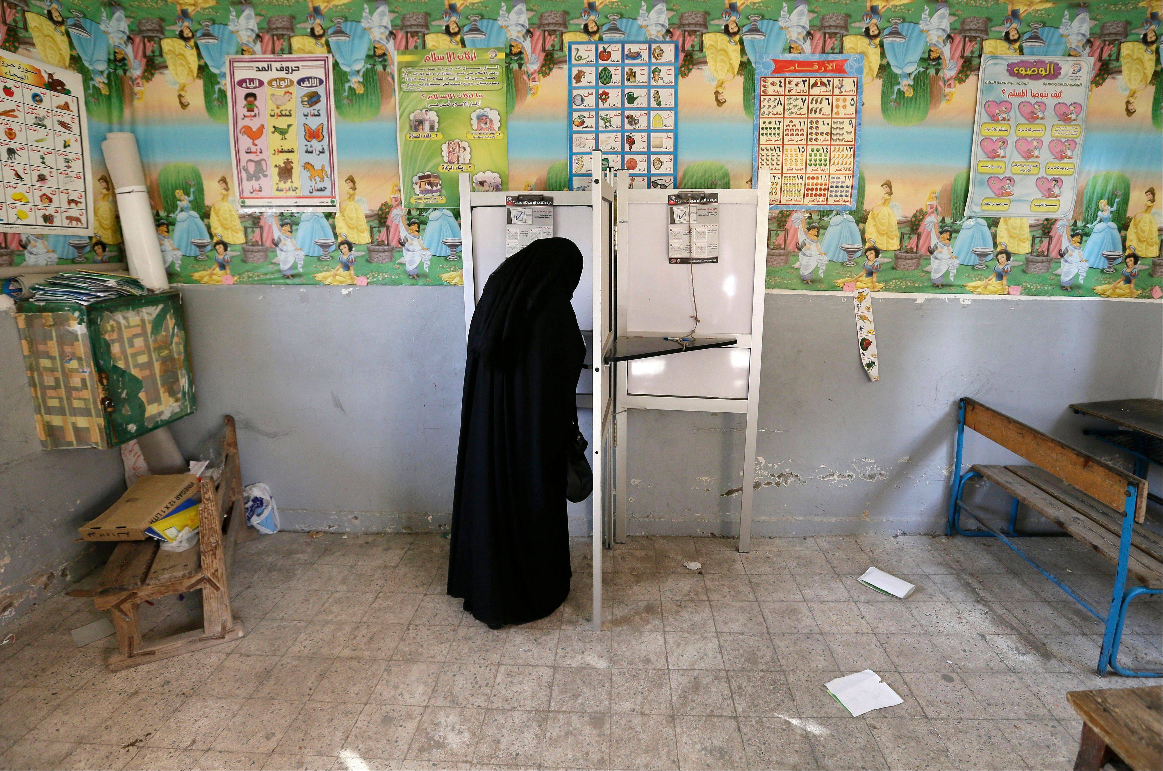 An Egyptian woman casts her vote at polling center Saturday during a referendum on a disputed constitution.