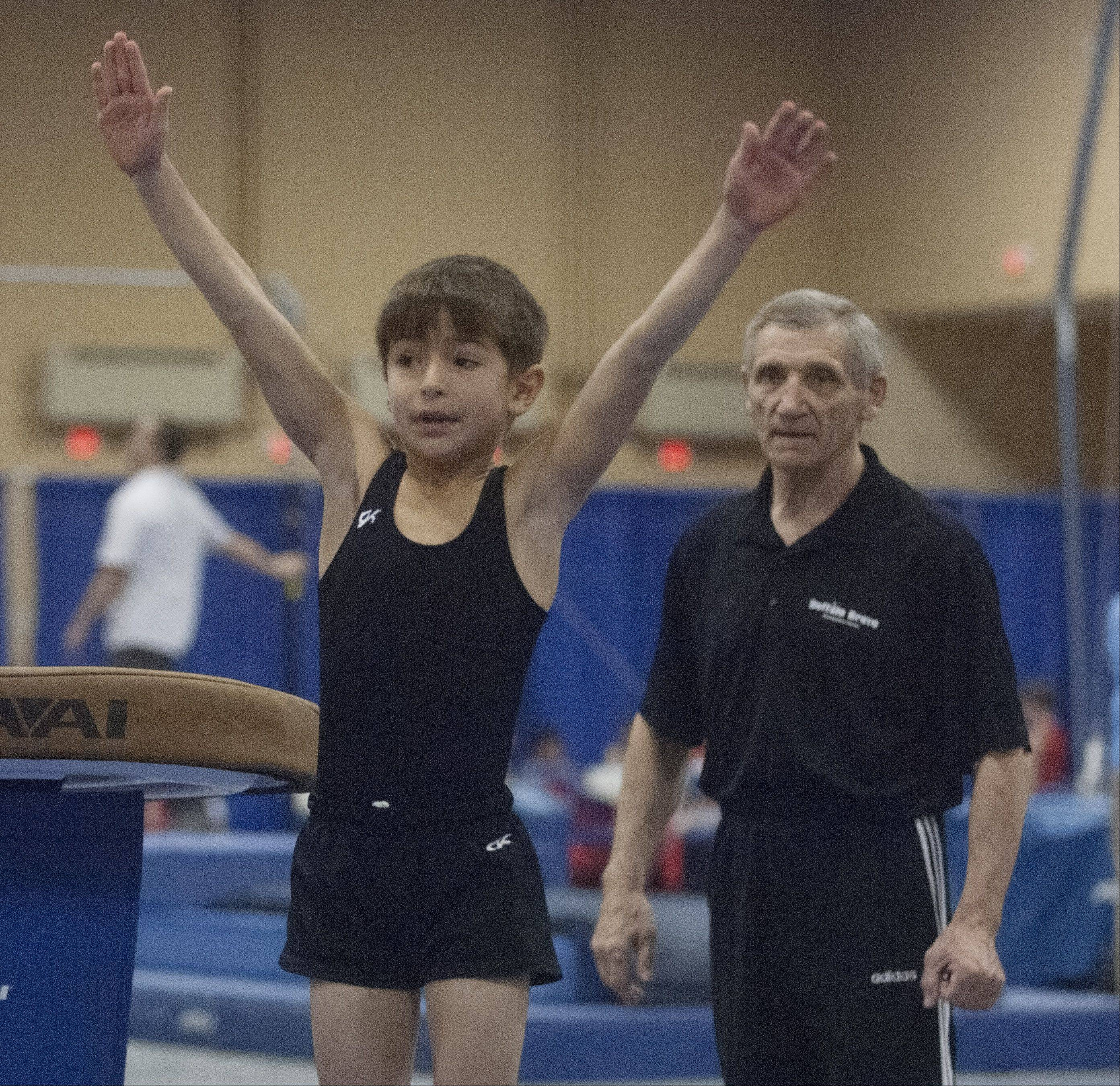 With coach Yevgeniy Vovkiv watching, Benjamin Valak of the Buffalo Grove Gymnastic Center turns toward the judge while competing on vault during the Hawaiian Pineapple Classic gymnastics meet, held at the Schaumburg Convention Center Saturday.