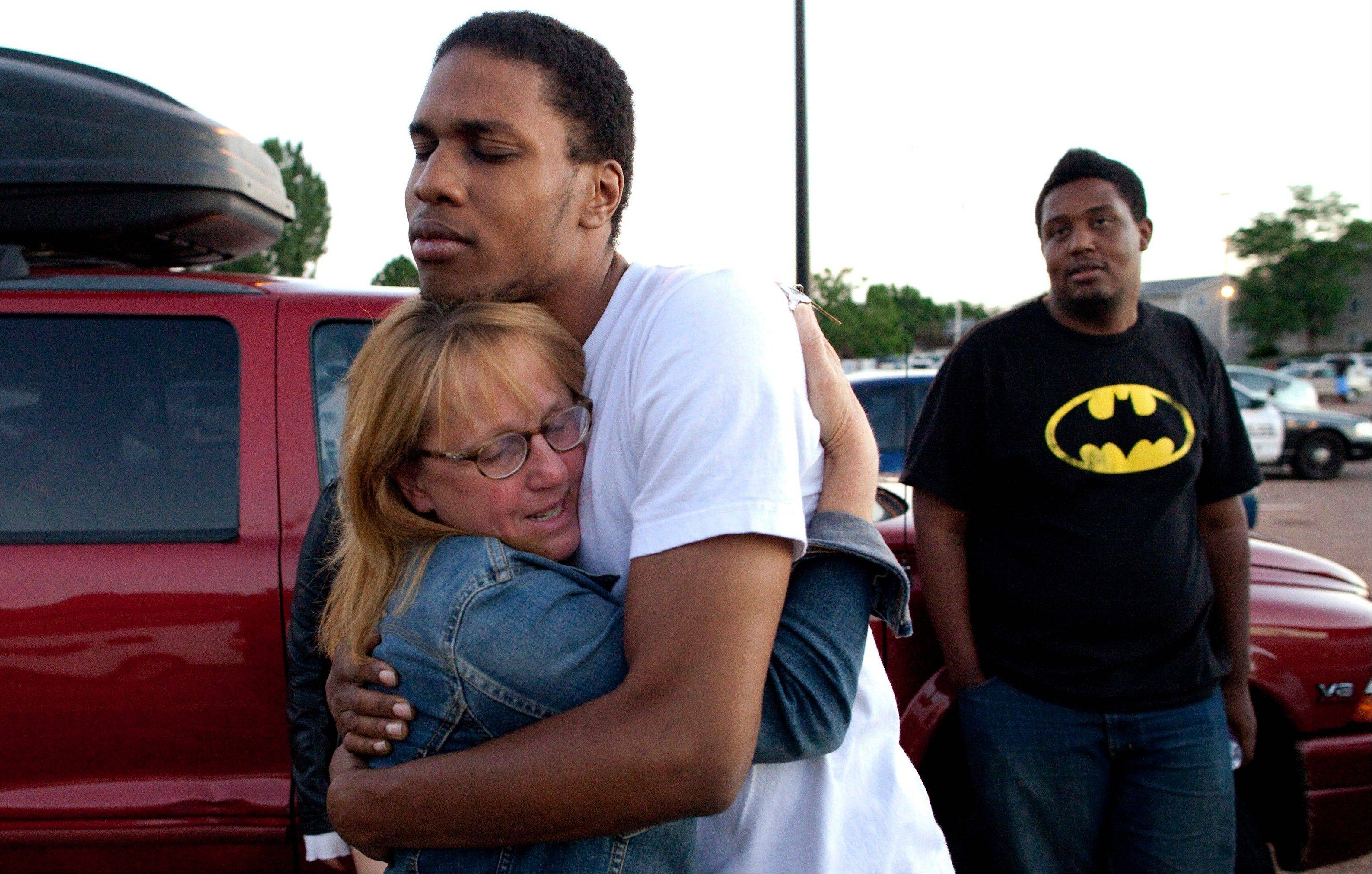 "Judy Goos, left, hugs her daughter's friend, Isaiah Bow, 20, an eyewitnesses, as Terrell Wallin, 20, right, looks on, outside Gateway High School where witnesses were brought for questioning after a gunman opened fire at the midnight premiere of the ""Dark Knight Rises"" movie in Aurora, Colo."