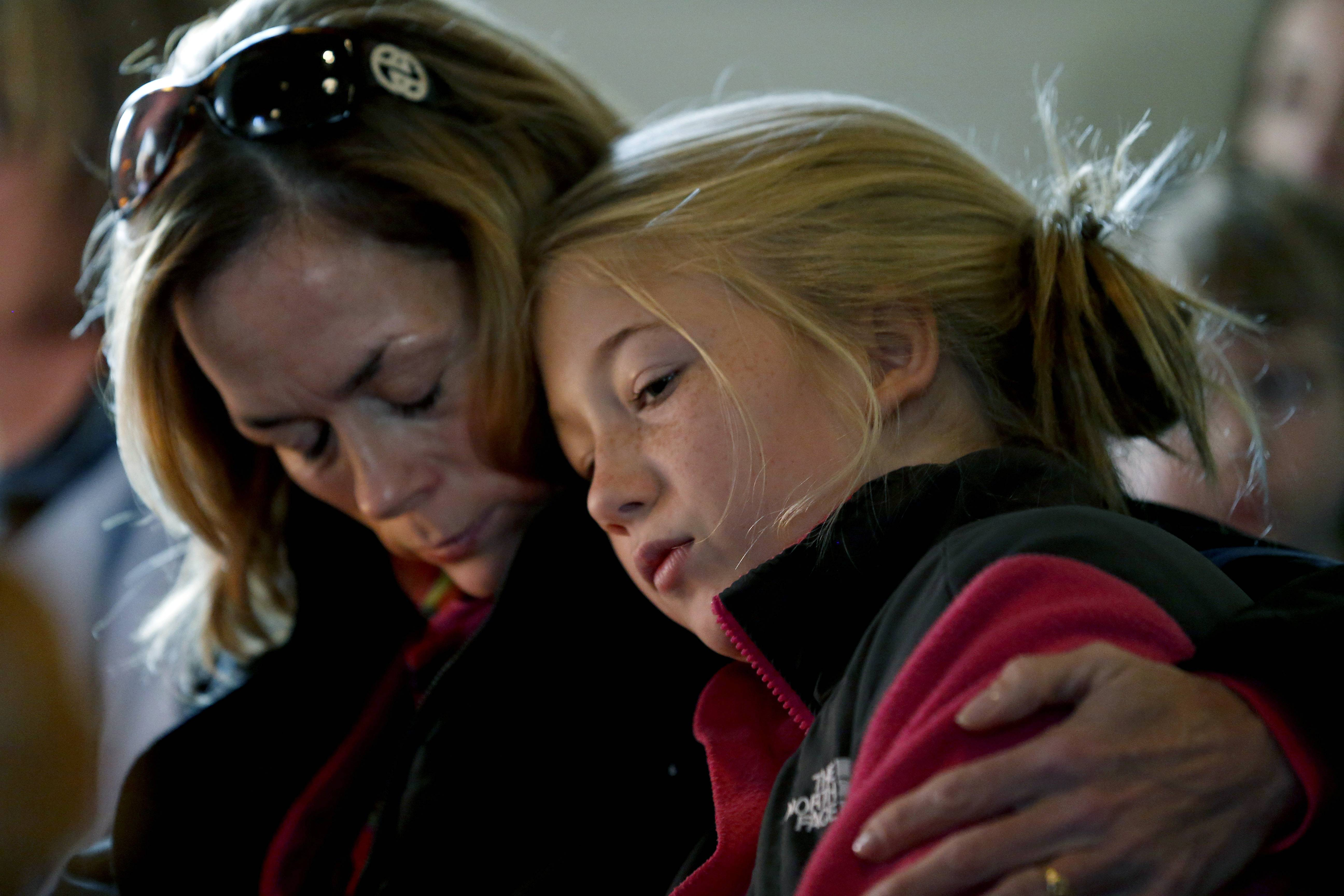 Molly Delaney, left, holds her 11-year-old daughter, Milly Delaney, Saturday during a service in honor of the victims who died a day earlier when a gunman opened fire at Sandy Hook Elementary School in Newtown, Conn.