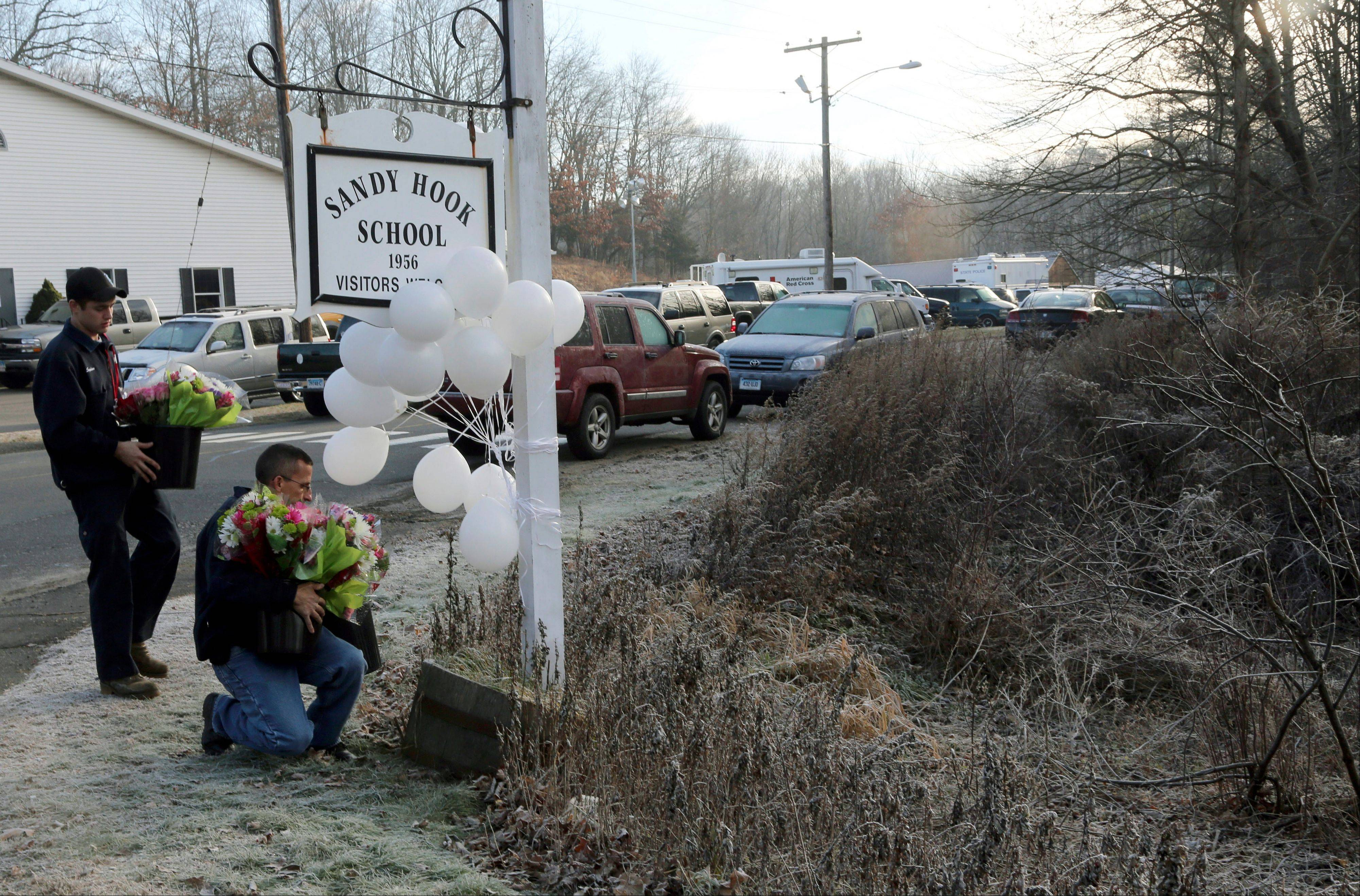 A couple of volunteer firefighters place flowers at a makeshift memorial at a sign for the Sandy Hook Elementary school, Saturday, Dec. 15, in Sandy Hook village of Newtown, Conn. The massacre of 26 children and adults at Sandy Hook Elementary school elicited horror and soul-searching around the world even as it raised more basic questions about why the gunman would have been driven to such a crime and how he chose his victims.