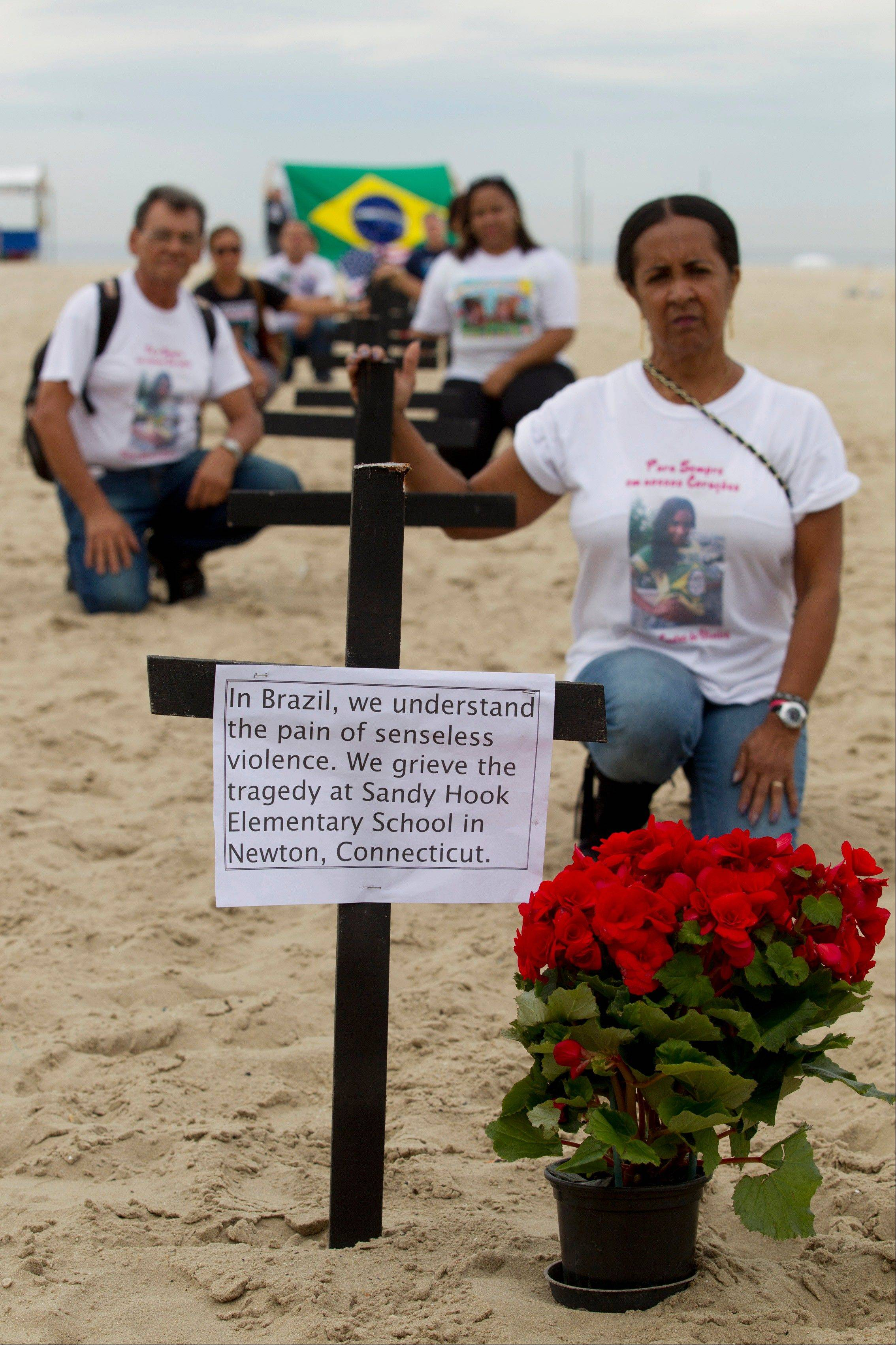 Relatives of victims of violent crimes stand near crosses at the Copacabana Beach, in Rio de Janeiro, in memory of the school shooting victims in Newtown, Conn. The massacre of 26 children and adults at Sandy Hook Elementary school elicited horror and soul-searching around the world.