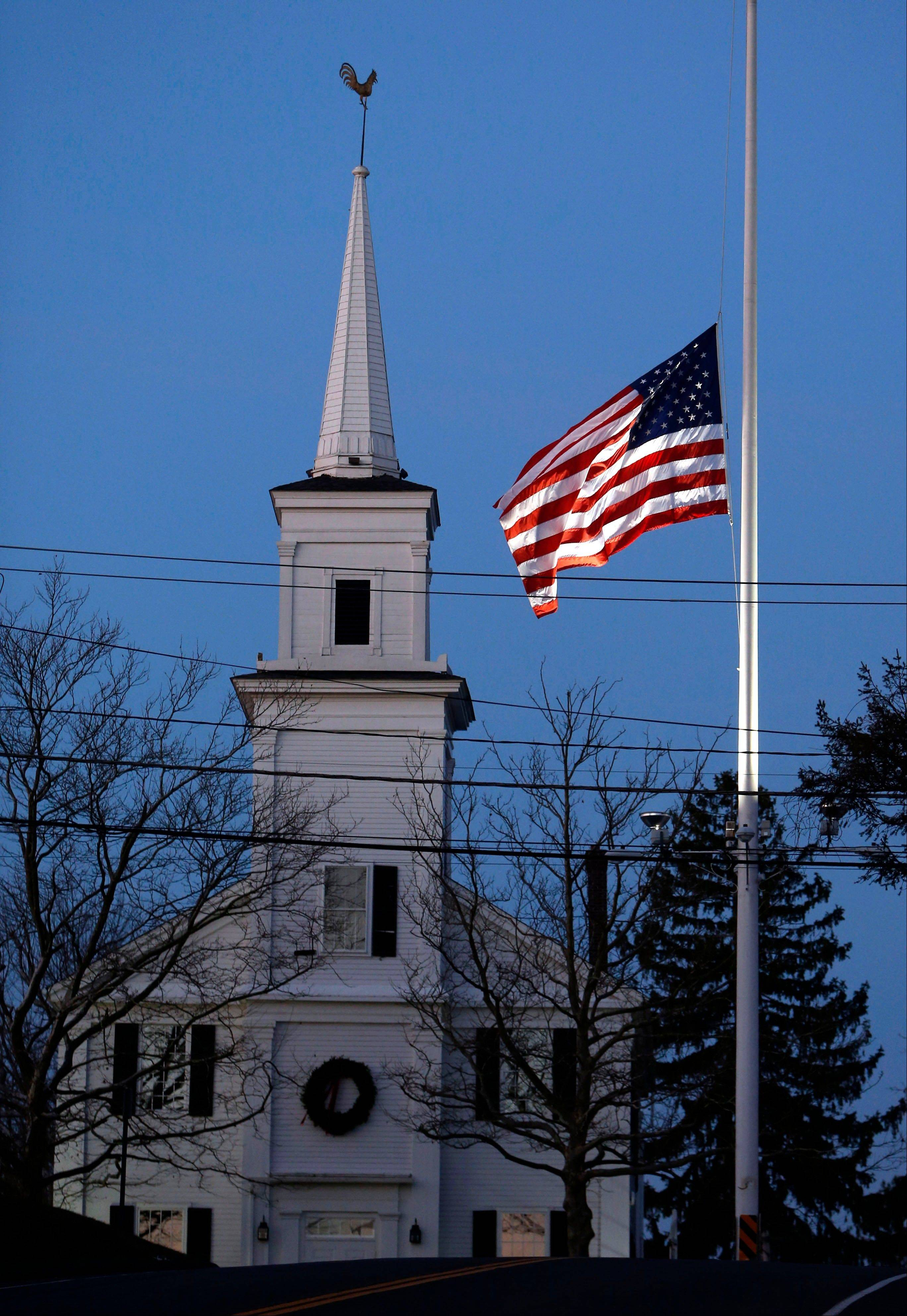 An American flag flies at half-staff as dawn breaks, Saturday, Dec. 15, in Newtown, Conn. A gunman walked into Sandy Hook Elementary School in Newtown Friday and opened fire, killing 26 people, including 20 children.
