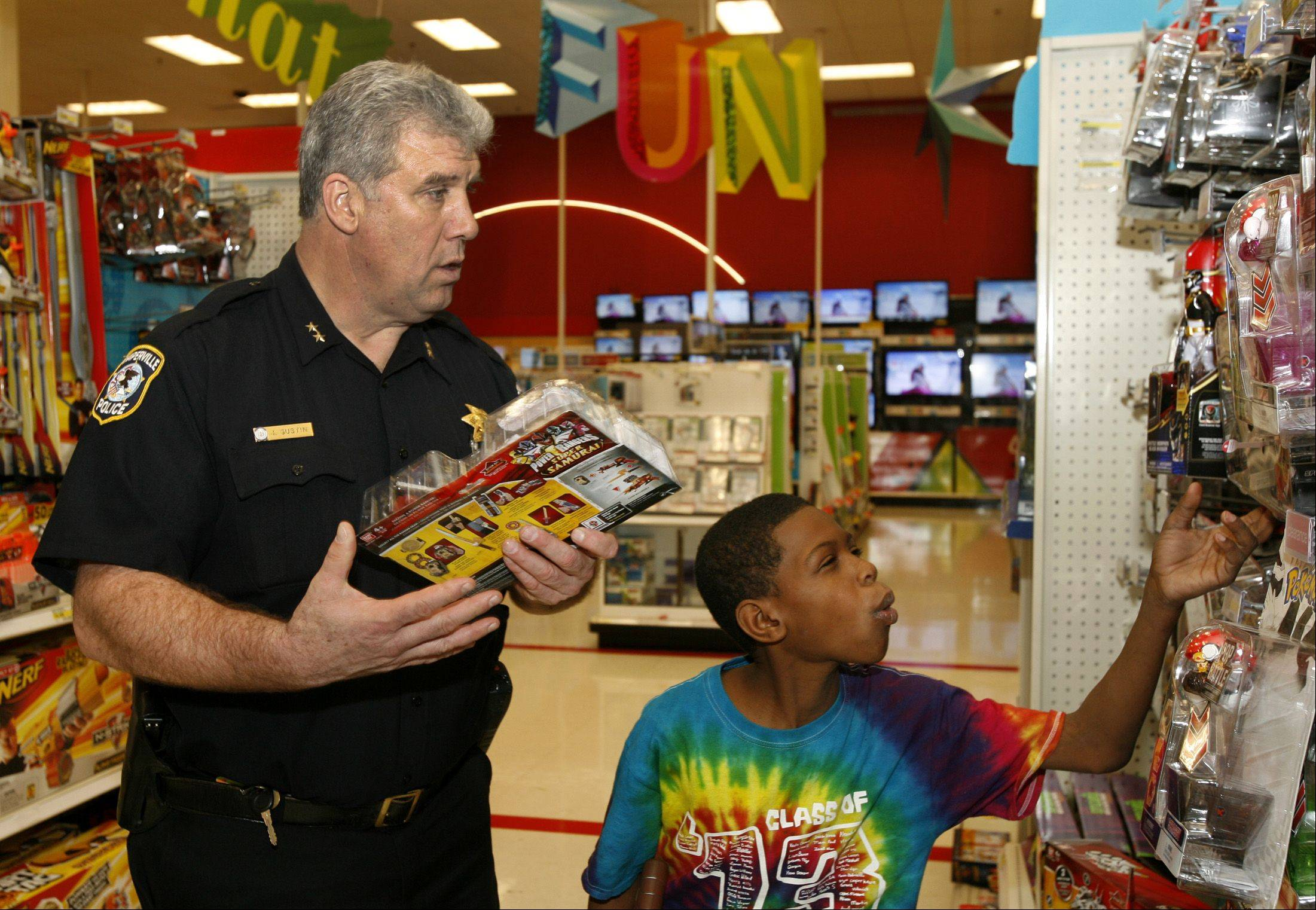 The NFOP in conjunction with the City of Naperville's youth services unit, select several disadvantaged children to participate in a $150.00 shopping spree. Darrell Ware, 10, of Naperville is teamed up with Naperville Deputy Chief John Gustin, who guides a shopping at a Naperville Target Store.