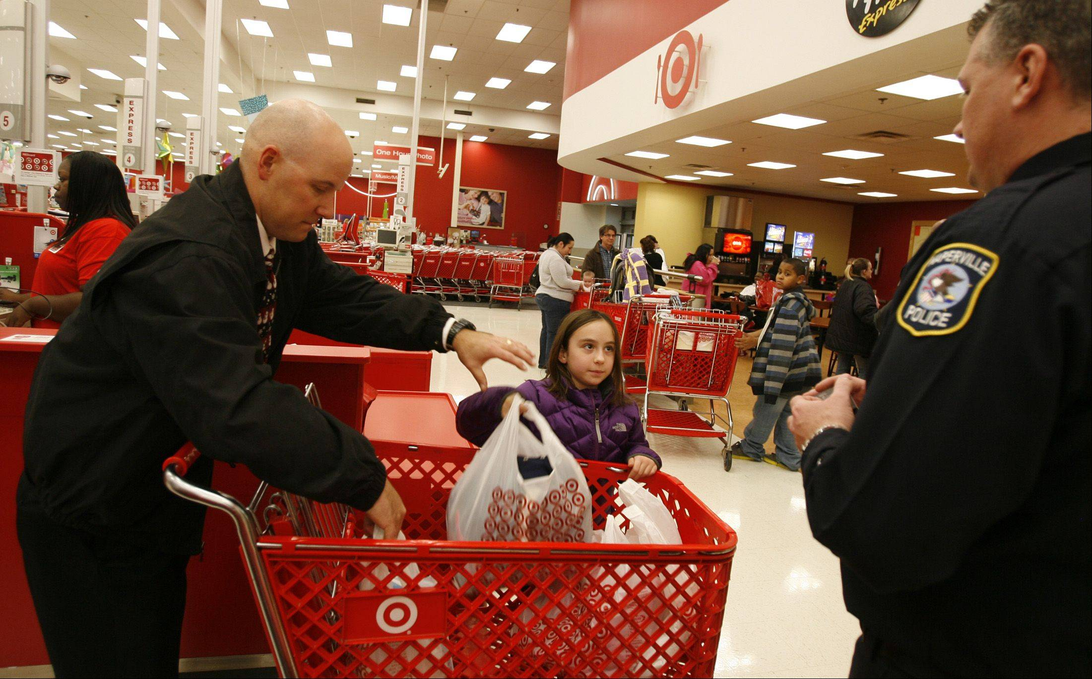 Marilyn Siwek, 8, of Naperville, checks out with Naperville Police officer Paul Elliott, left, and Vince Clark, right, who help guide a shopping spree at a Naperville Target Store.