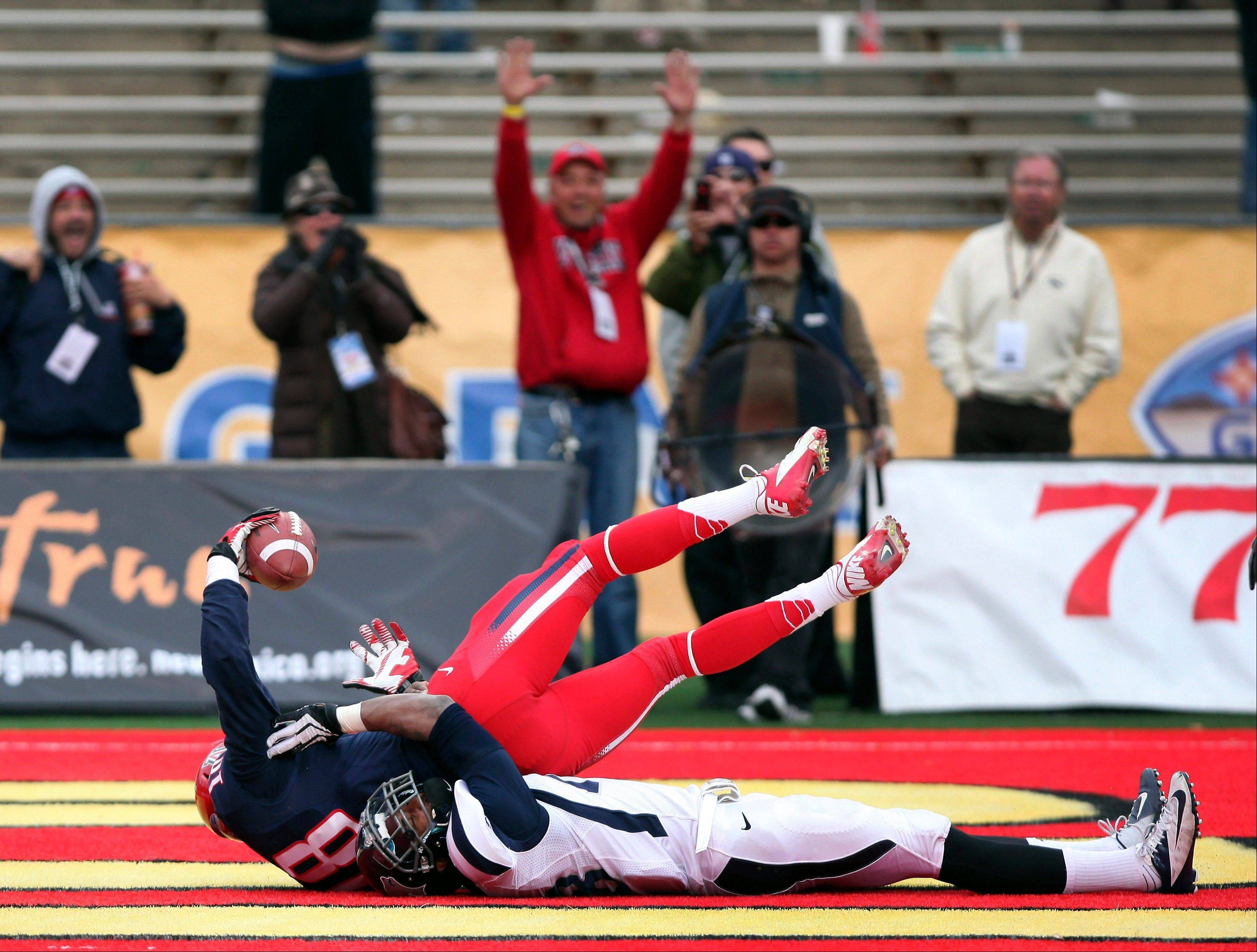 Arizona's Terrance Miller comes down with a touchdown catch in the end zone in front of Nevada's Bryson Keeton to tie the game in the closing seconds of the fourth quarter of New Mexico Bowl Saturday in Albuquerque, N.M. Arizona won 49-48.