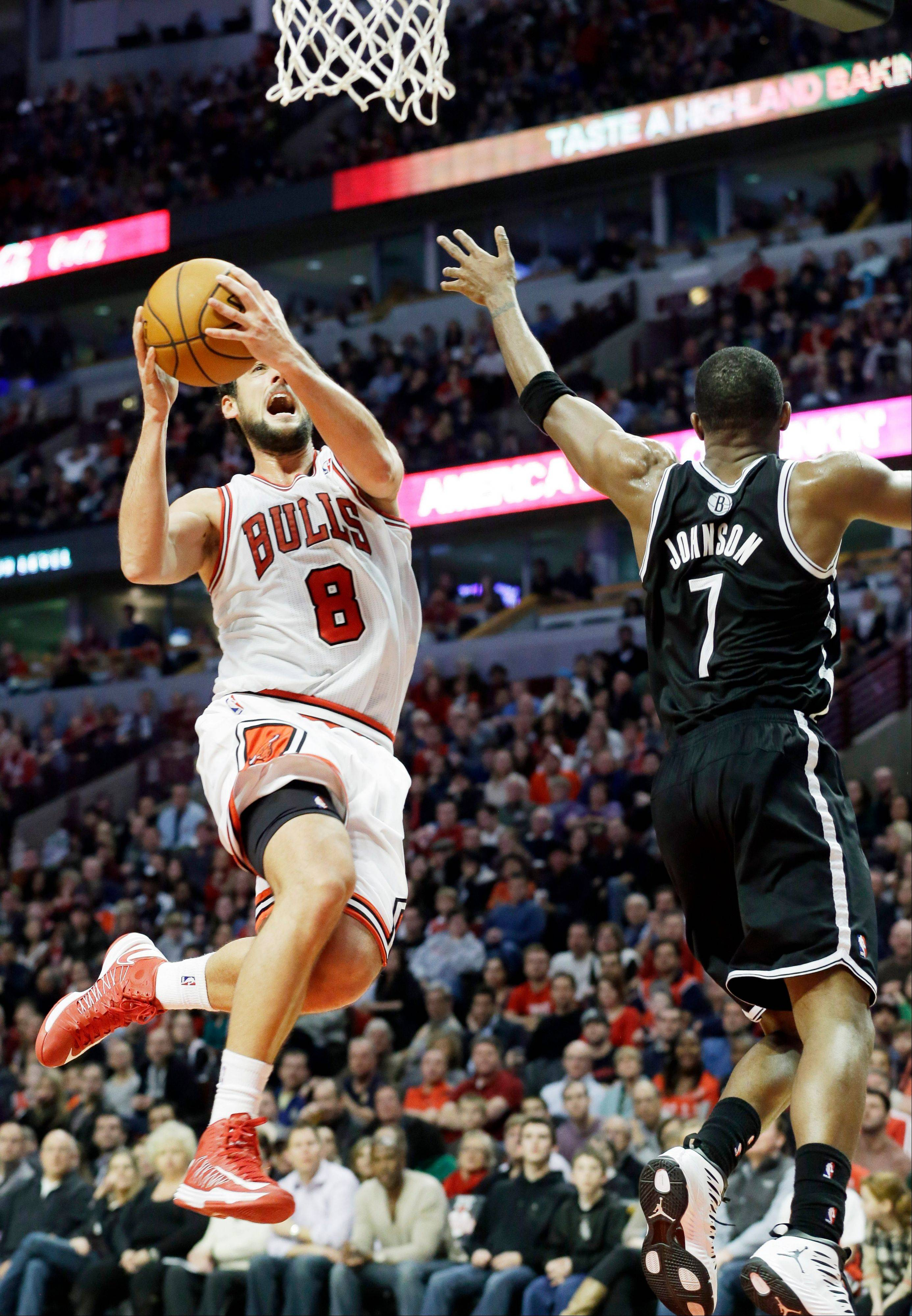 Marco Belinelli, of, Italy, left, drives to the basket against Brooklyn Nets guard Joe Johnson during the second half of an NBA basketball game in Chicago on Saturday, Dec. 15, 2012. The Bulls won 83-82.