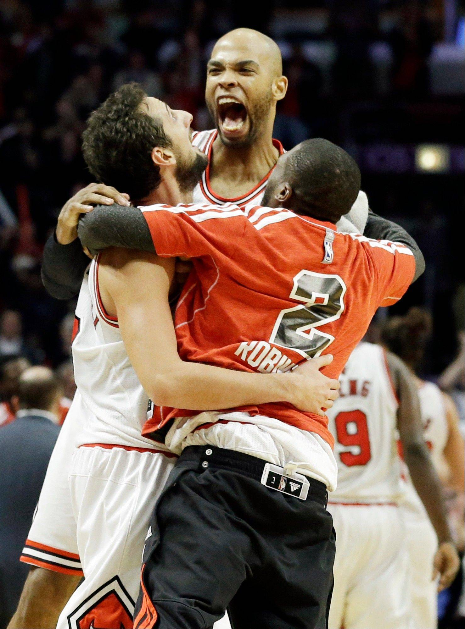 Marco Belinelli, left, celebrates with Taj Gibson, center, and Nate Robinson after scoring a basket during the second half of an NBA basketball game against the Brooklyn Nets in Chicago on Saturday, Dec. 15, 2012. The Bulls won 83-82.