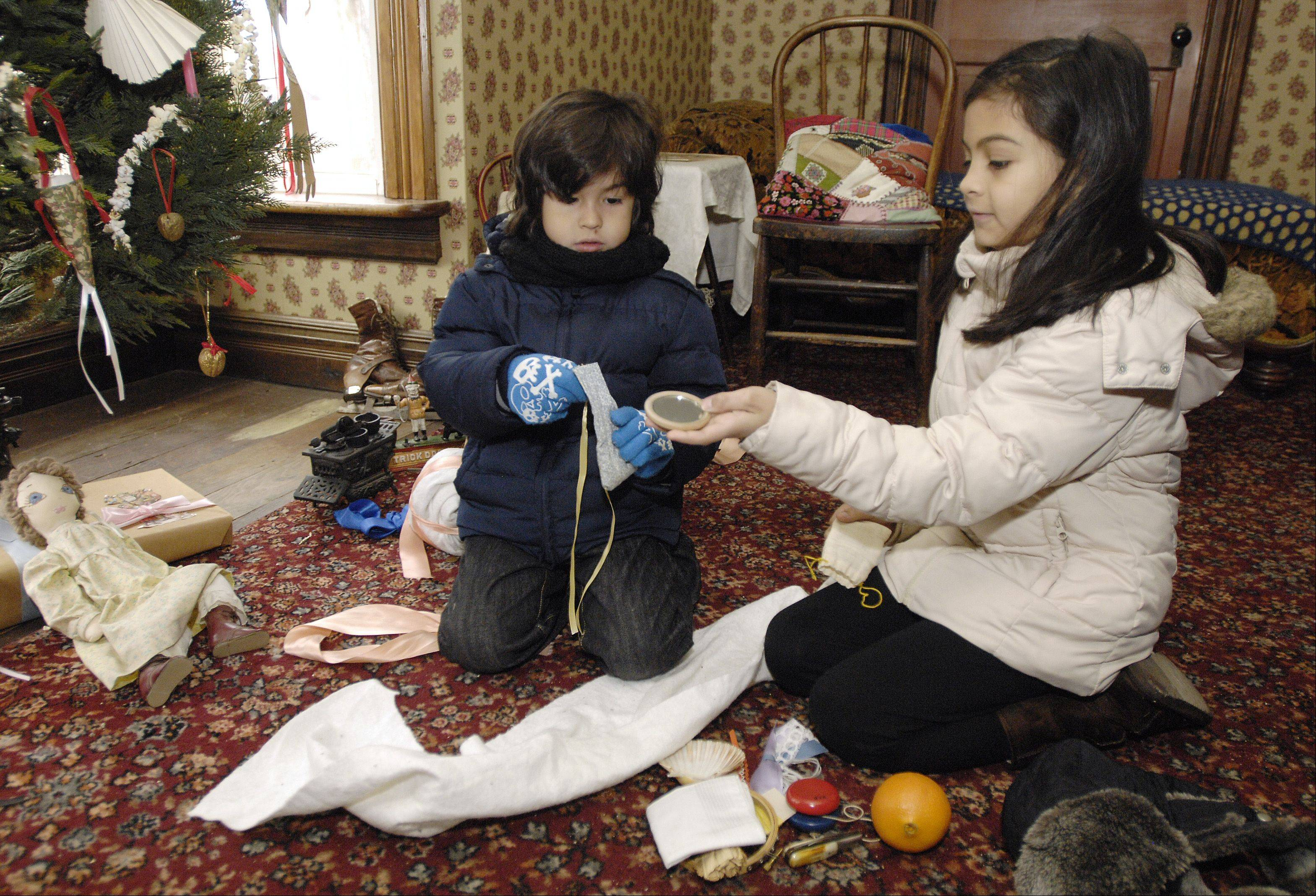 "Diego Vera, 6, of Carol Stream, and his sister, Leslie, 8, open a traditional 1890s Christmas gift call a ""snowball"" Sunday while visiting Kline Creek Farm in West Chicago for a historical interpretation of an 1890s DuPage County Christmas."
