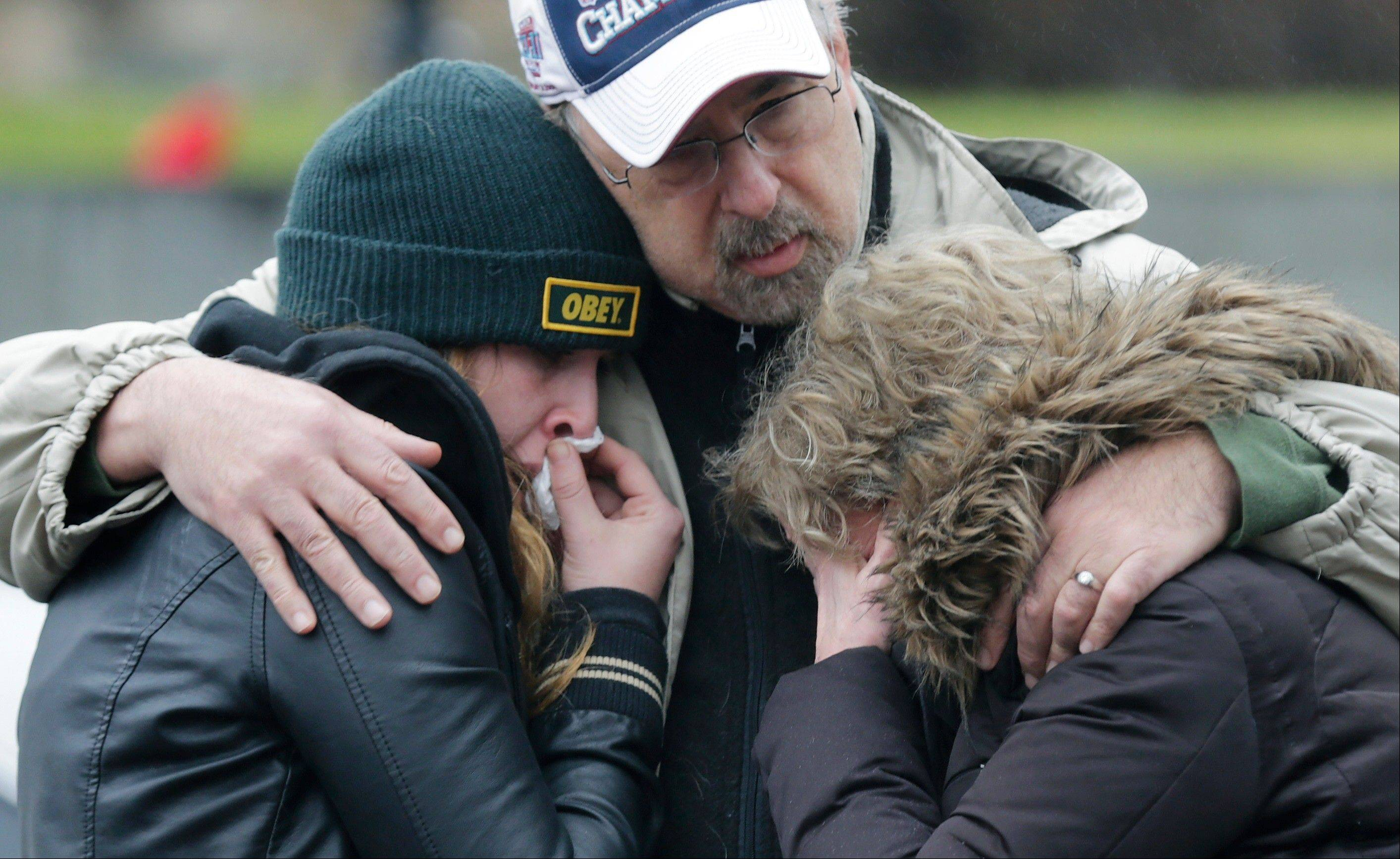 A man clutches two sobbing women at the site of a makeshift memorial for school shooting victims at the village of Sandy Hook in Newtown, Conn., Sunday, Dec. 16, 2012. A gunman opened fire at Sandy Hook Elementary School in the town, killing 26 people, including 20 children before killing himself on Friday.