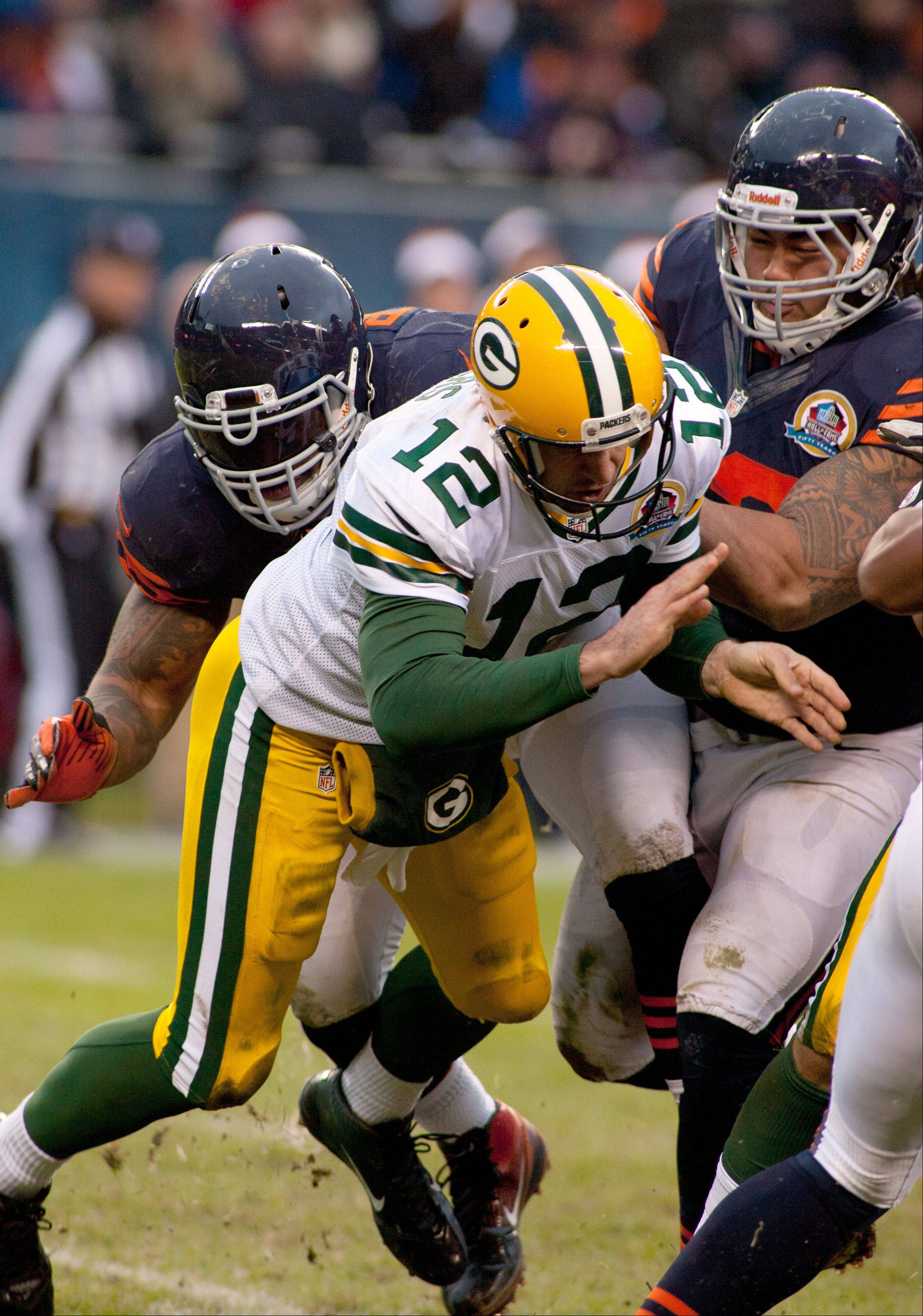 The Packer�s Aaron Rodgers is hit by the Bears� Julius Peppers, who was called for roughing the passer on the play, during Sunday�s game at Soldier Field in Chicago.