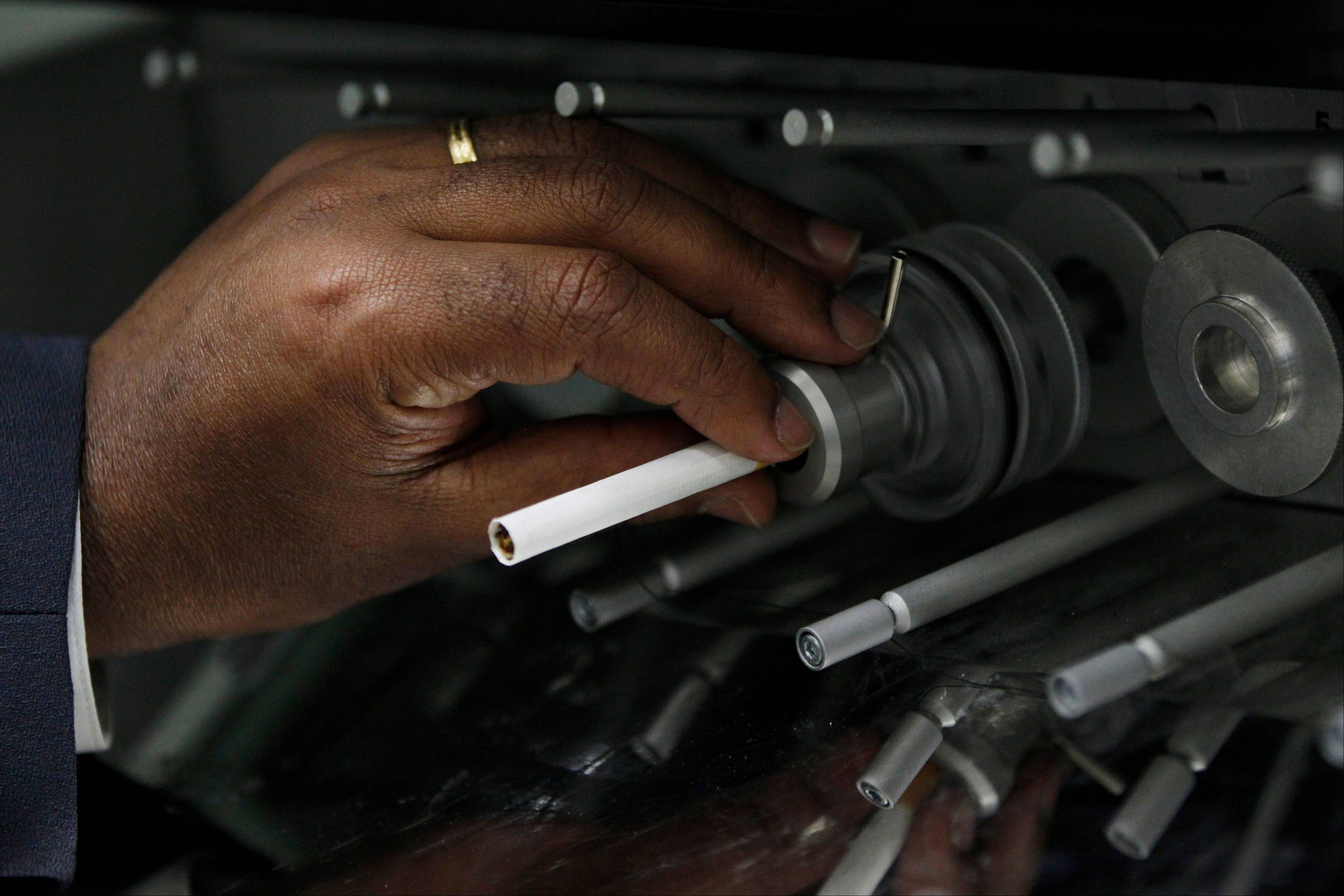 A cigarette is positioned in a mainstream linear 20-port smoking machine at the U.S. Department of Treasury's Alcohol and Tobacco Tax and Trade Bureau laboratory, in Beltsville, Md. The Alcohol and Tobacco Tax and Trade Bureau, which collects taxes on booze and smokes and tells the companies that produce them how to do business, is one example of the specialized government offices threatened by Washingtonís current zeal for cost-cutting.