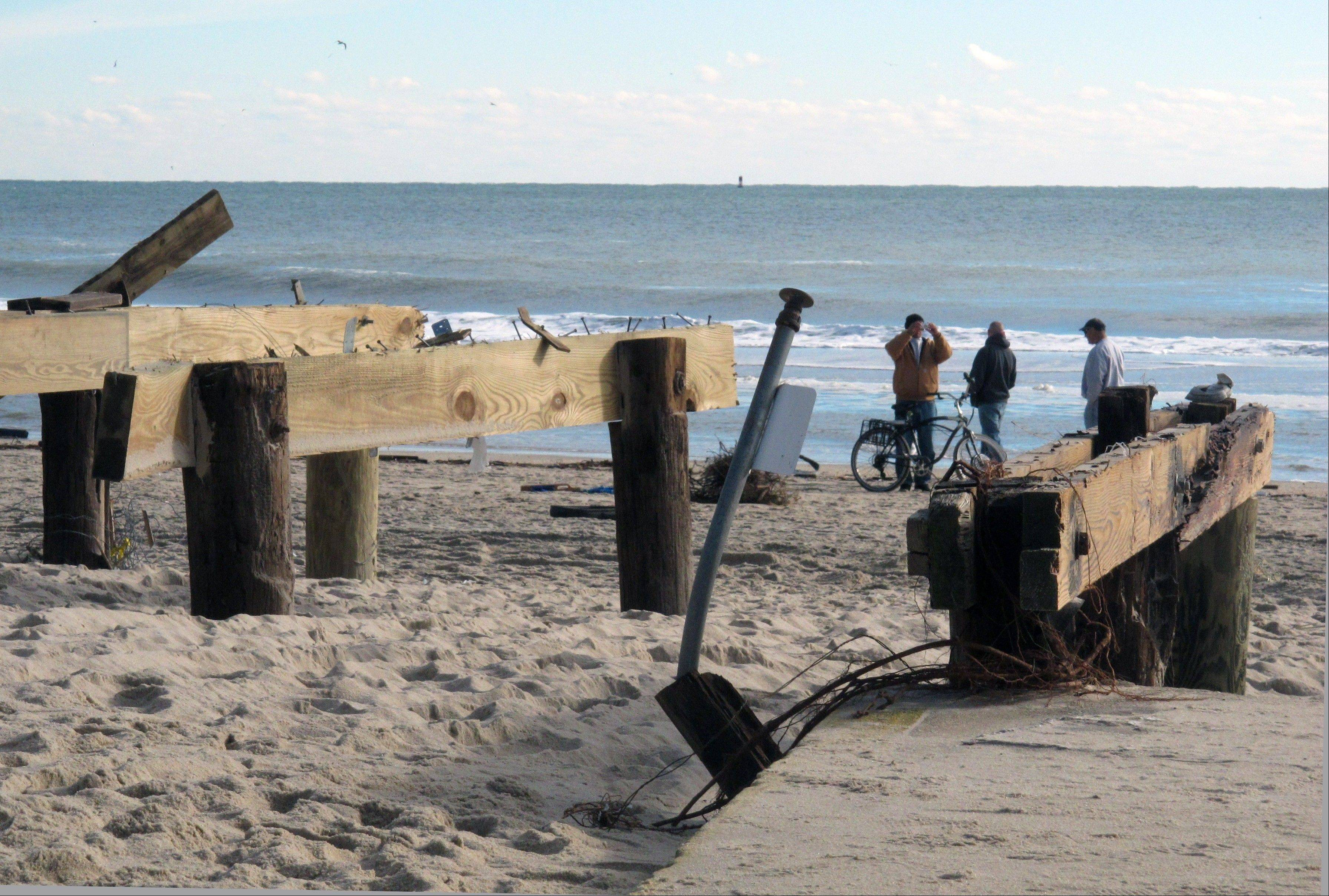 Teens on the beach at Point Pleasant Beach, N.J., next to pilings that used to support part of a boardwalk that was washed away by Superstorm Sandy. Coastal towns are racing to repair their boardwalks in time for next summer.
