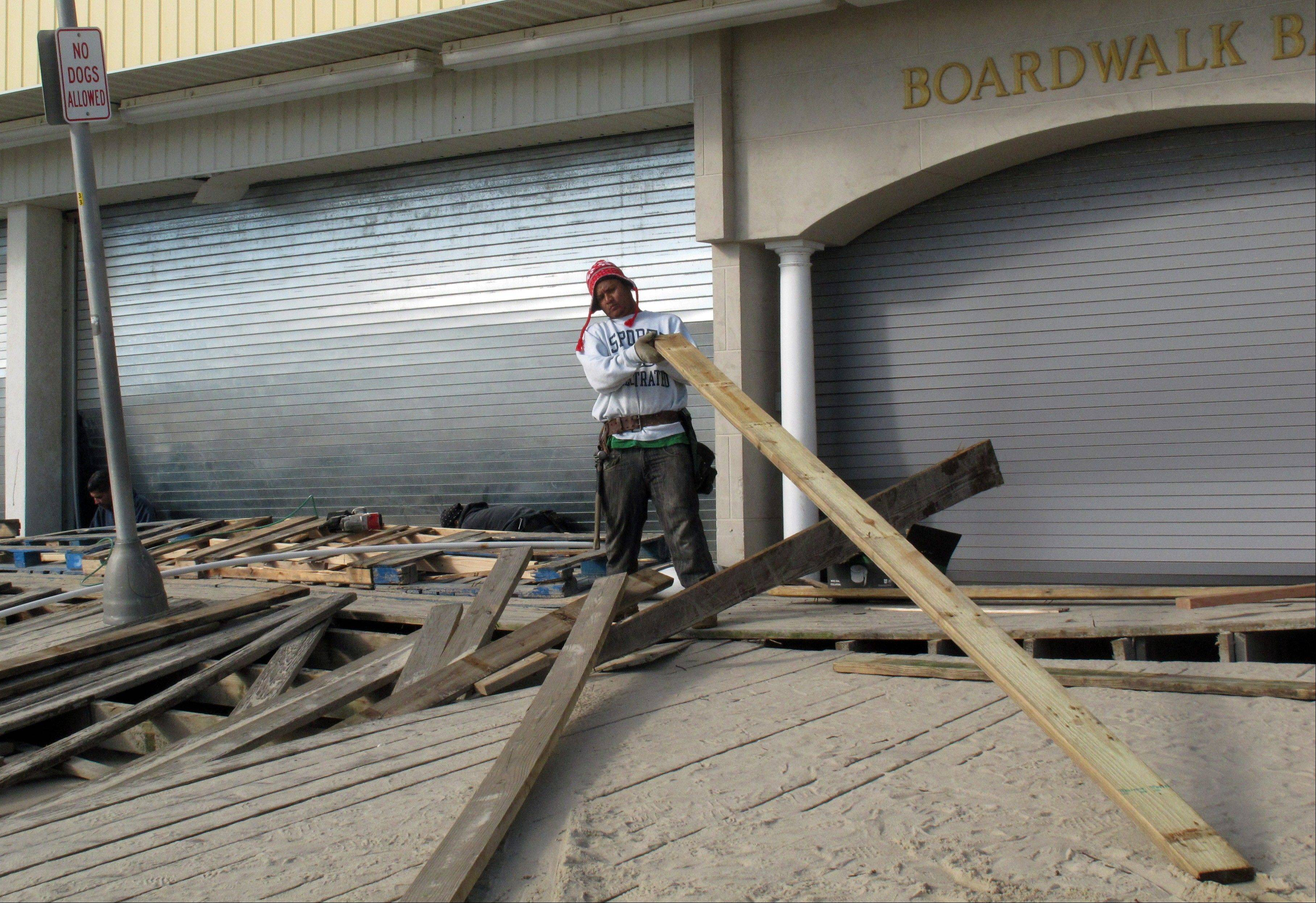 A worker removes damaged boards from the Point Pleasant Beach, N.J., boardwalk, three days after Superstorm Sandy wrecked parts of it. Coastal communities are racing to rebuild their boardwalks in time for next summer.